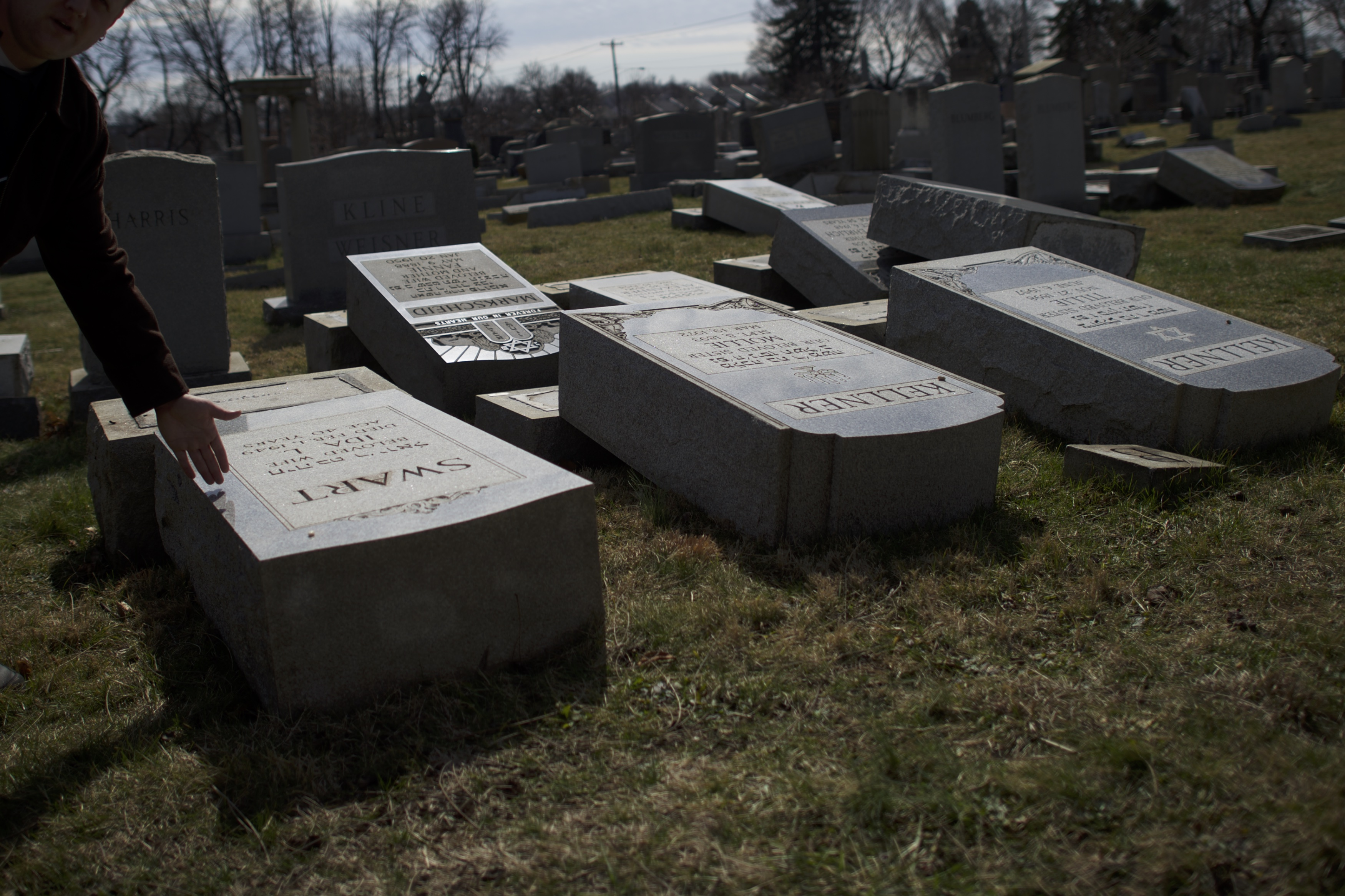 A man motions towards Jewish tombstones vandalized at Mount Carmel Cemetery February 27, 2017 in Philadelphia,