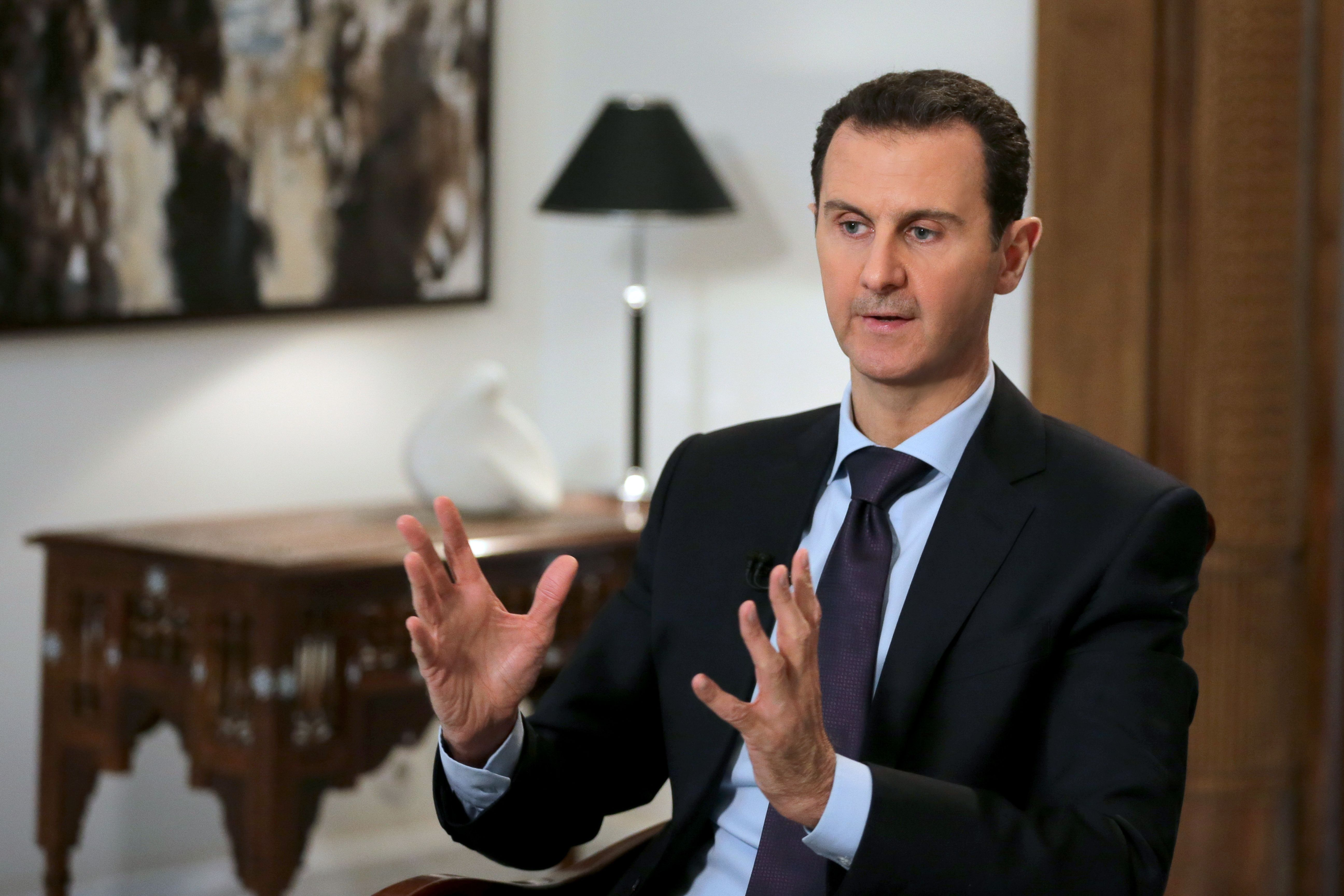Syrian President Bashar al-Assad gestures during an exclusive interview in the capital Damascus on February 11, 2016.