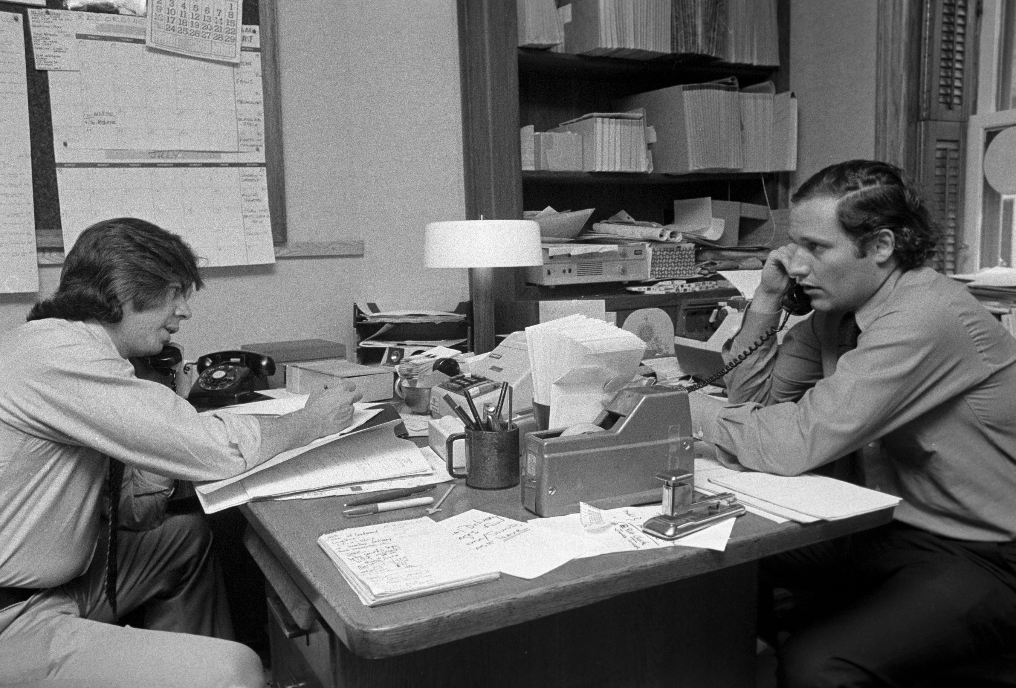 Journalists Carl Bernstein (L) and Bob Woodward (R), whose reporting on the Watergate incident won a Pulitzer Prize, making phone calls on June 17, 1974 in New York City.