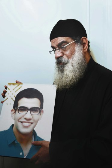 """Father Daniel Maher, 53, a priest at St. George's church, holds a photo of his slain son Beshoy, 23, who died at the church bombing in Tanta Egypt on April 9, 2017. """"Beshoy was in front of me the whole time during the Palm Sunday service. The moment I got up into the church's alter, the explosion happened,"""" Father Daniel said. """"A [piece of] shrapnel got into his brain and his brother was set on fire."""""""