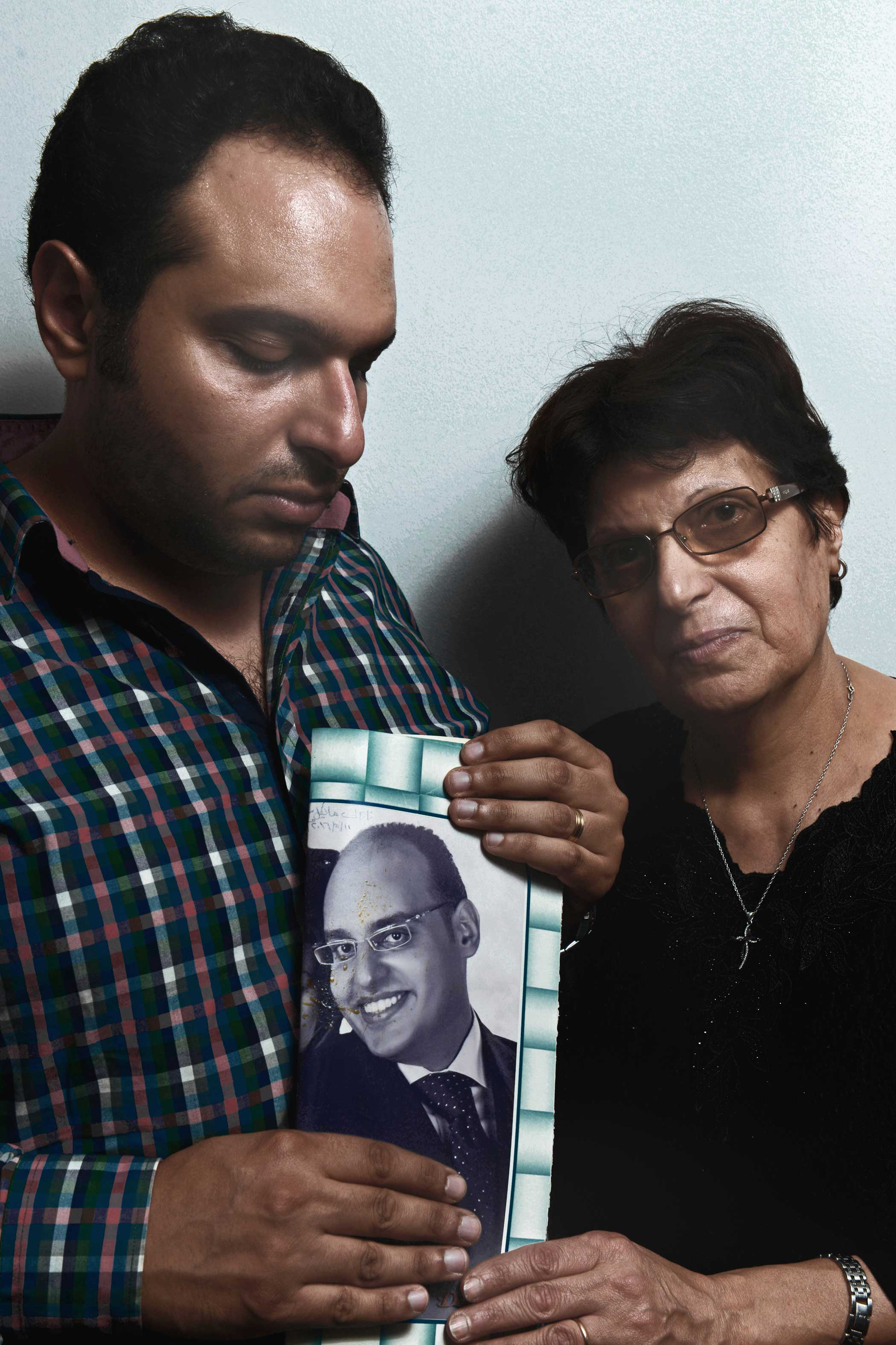 Mark Samir Iskander, 30, and Salwa Nemr Youssef, 60, hold a photo of Michael Samir Iskander, 36. Michael was Mark's brother and Salwa's son.  I rushed into the church when I heard the news. We could not find his body [in] the church. After looking for hours in hospitals, we found his body in the morgue,  Mark said.  Michael was the father of the house the moment his father passed away,  Salwa added.  He was my everything.