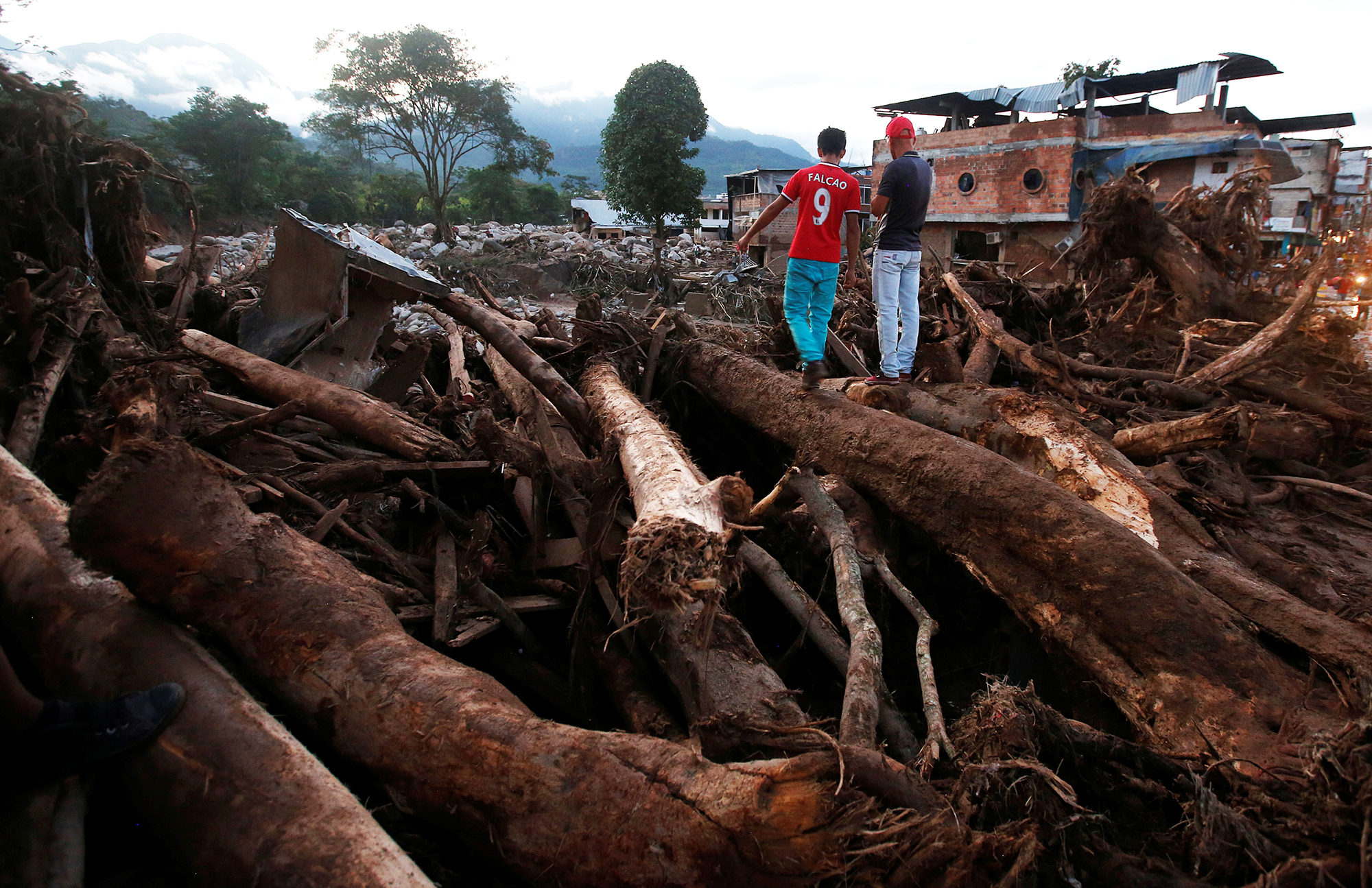 Men look at a destroyed area afterwards heavy rains caused several rivers to overflow, pushing sediment and rocks into buildings and roads in Mocoa, Colombia, on April 1, 2017.