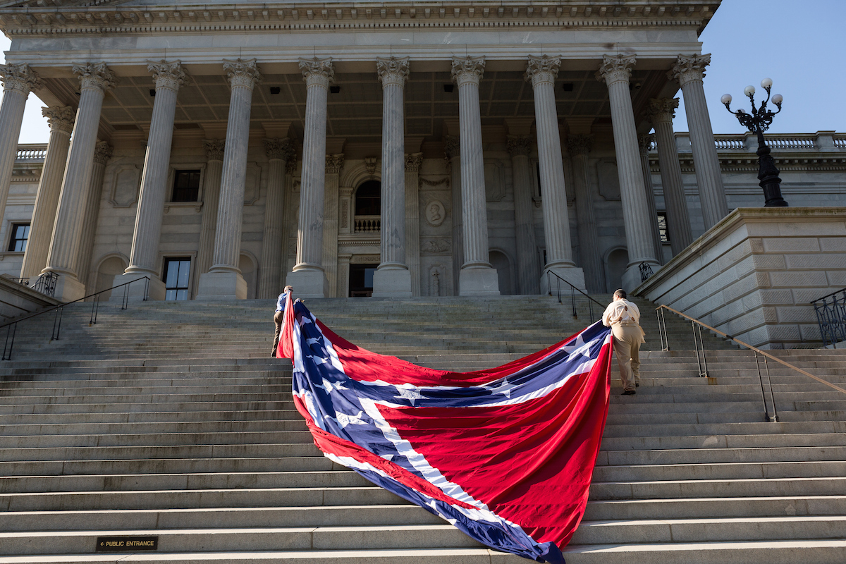 Confederate re-enactors position a gigantic Confederate flag on the steps of the South Carolina State Capitol building on May 2, 2015 in Columbia, S.C. Confederate Memorial Day is a official state holiday in South Carolina and honors those that served during the Civil War.