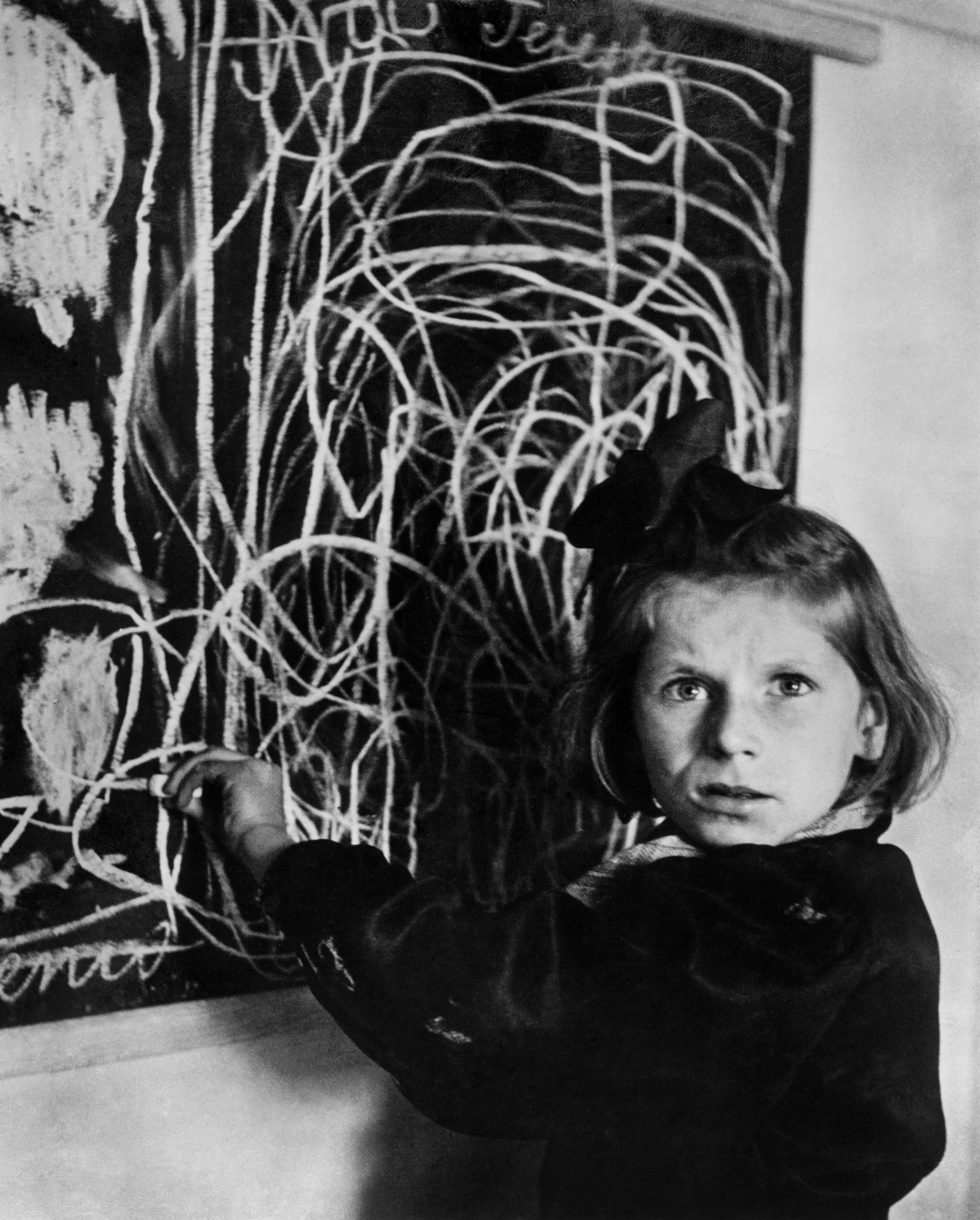 Tereska, a child in a residence for disturbed children. She drew a picture of  home  on the blackboard. Warsaw, 1948.