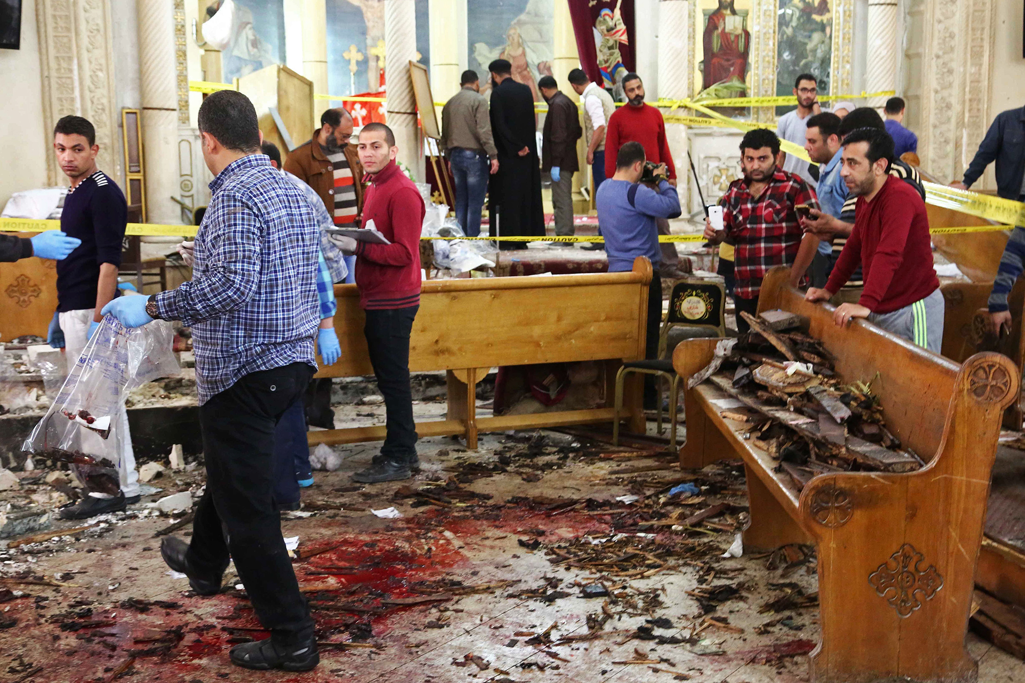 Forensics analysts collect evidence at the site of a bomb blast, which struck worshippers gathering to celebrate Palm Sunday at the Mar Girgis Coptic Church in the Nile Delta City of Tanta, 75 miles north of Cairo, on April 9, 2017.