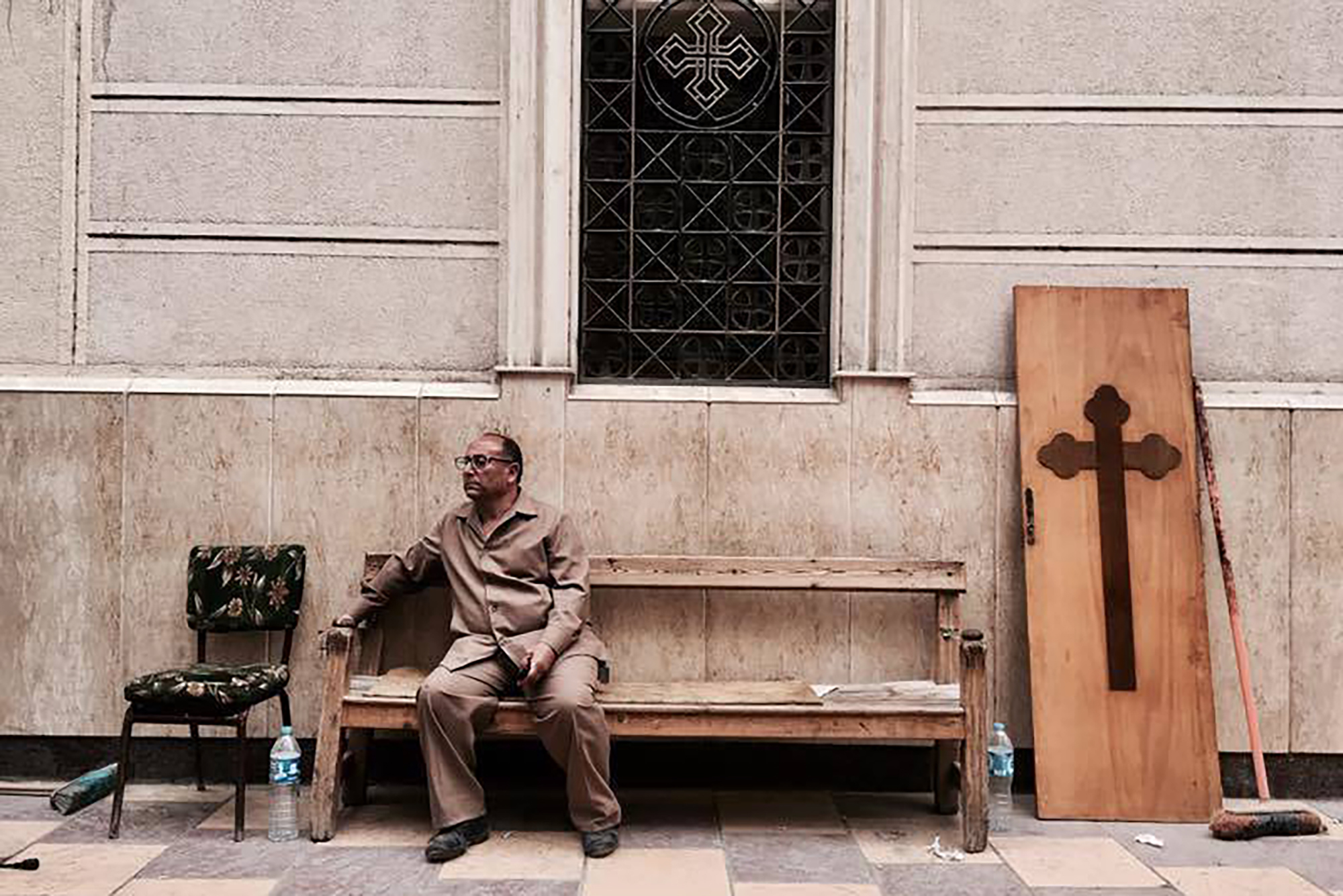 A man sits on a bench outside a church after a bomb attack in the Nile Delta town of Tanta, Egypt, on April 9, 2017.