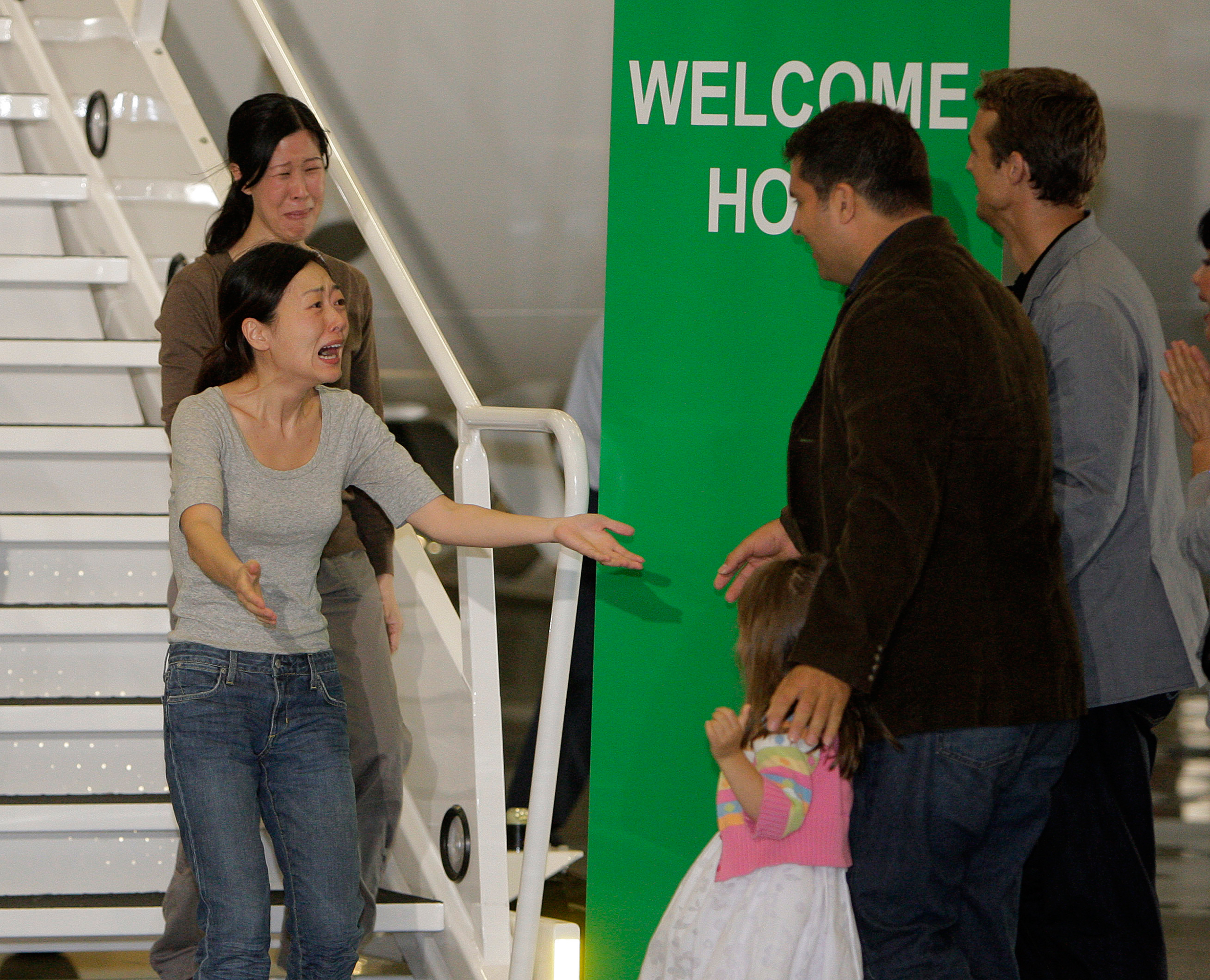 Euna Lee, left, and Laura Ling, are greeted by their husbands after their arrival at Bob Hope Airport in Burbank, Calif., on Aug. 5, 2009. The two American journalists had been arrested that March after allegedly crossing into North Korea from China.