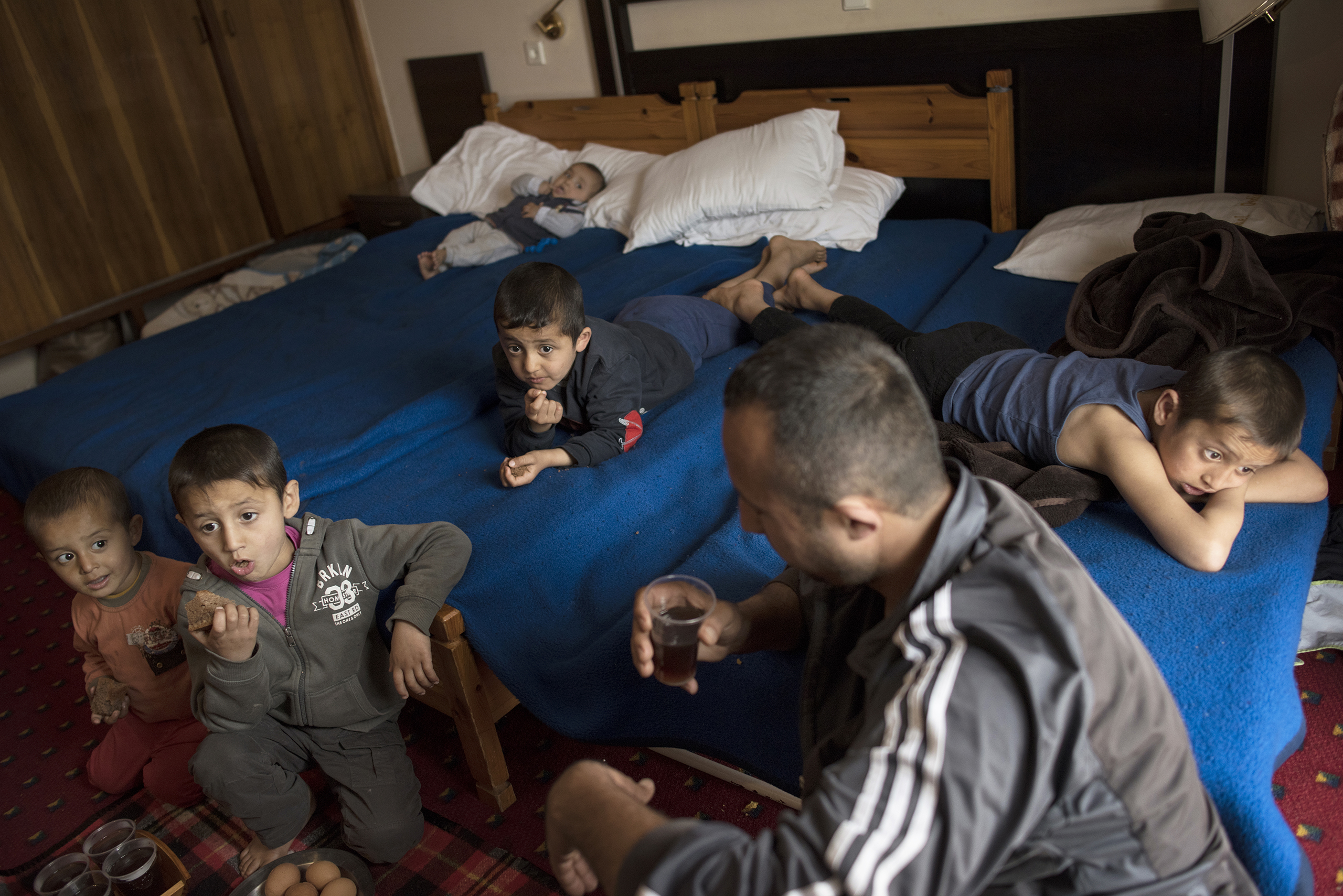 Minhel drinks tea while his children watch television in a hotel in Kastoria, Greece, near the Albanian border, March 27, 2017.