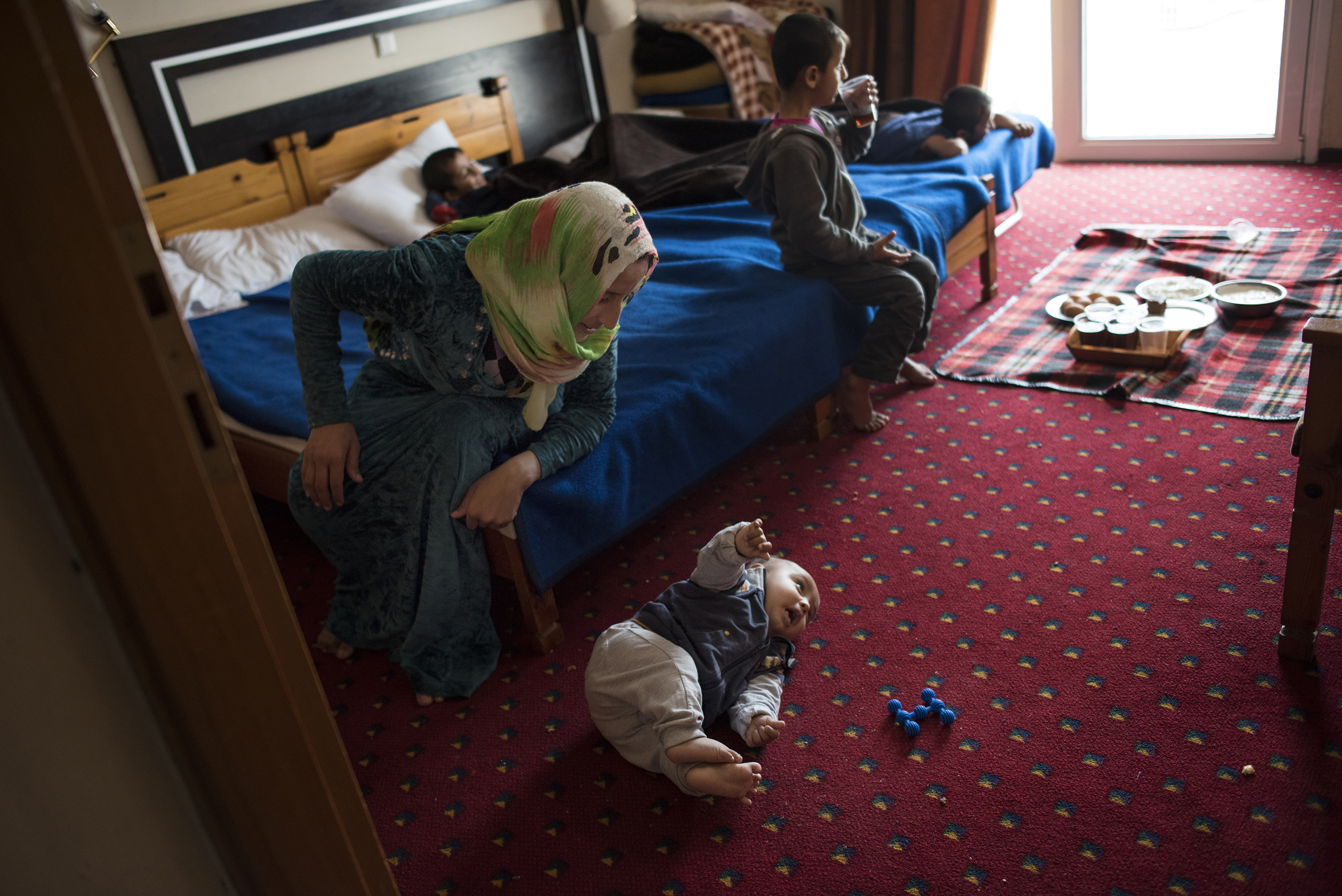 27-year-old Illham Saleh watches her six-month-old baby, Faraj, try to roll over while at a hotel in Kastoria, Greece, near the Albanian border, March 27, 2017.