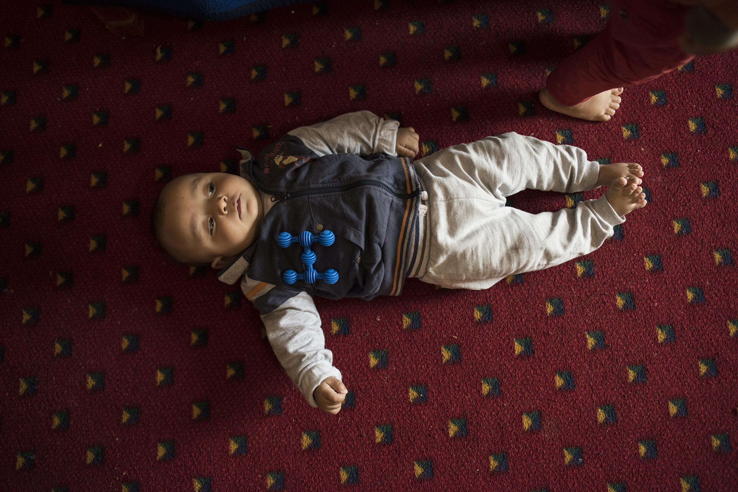 Faraj, now six months old, and the youngest son of 27-year-old Illham Saleh, takes a rest from trying to roll over on the floor at a hotel in Kastoria, Greece, near the Albanian border, March 27, 2017.