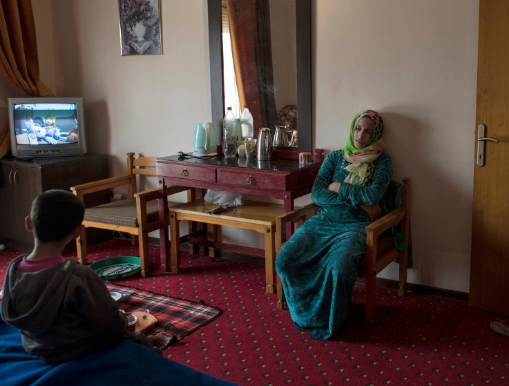 27-year-old Illham Saleh rests for a moment while her third son, Saleh, watches television, at a hotel in kastoria, Greece, near the Albanian border, March 27, 2017.