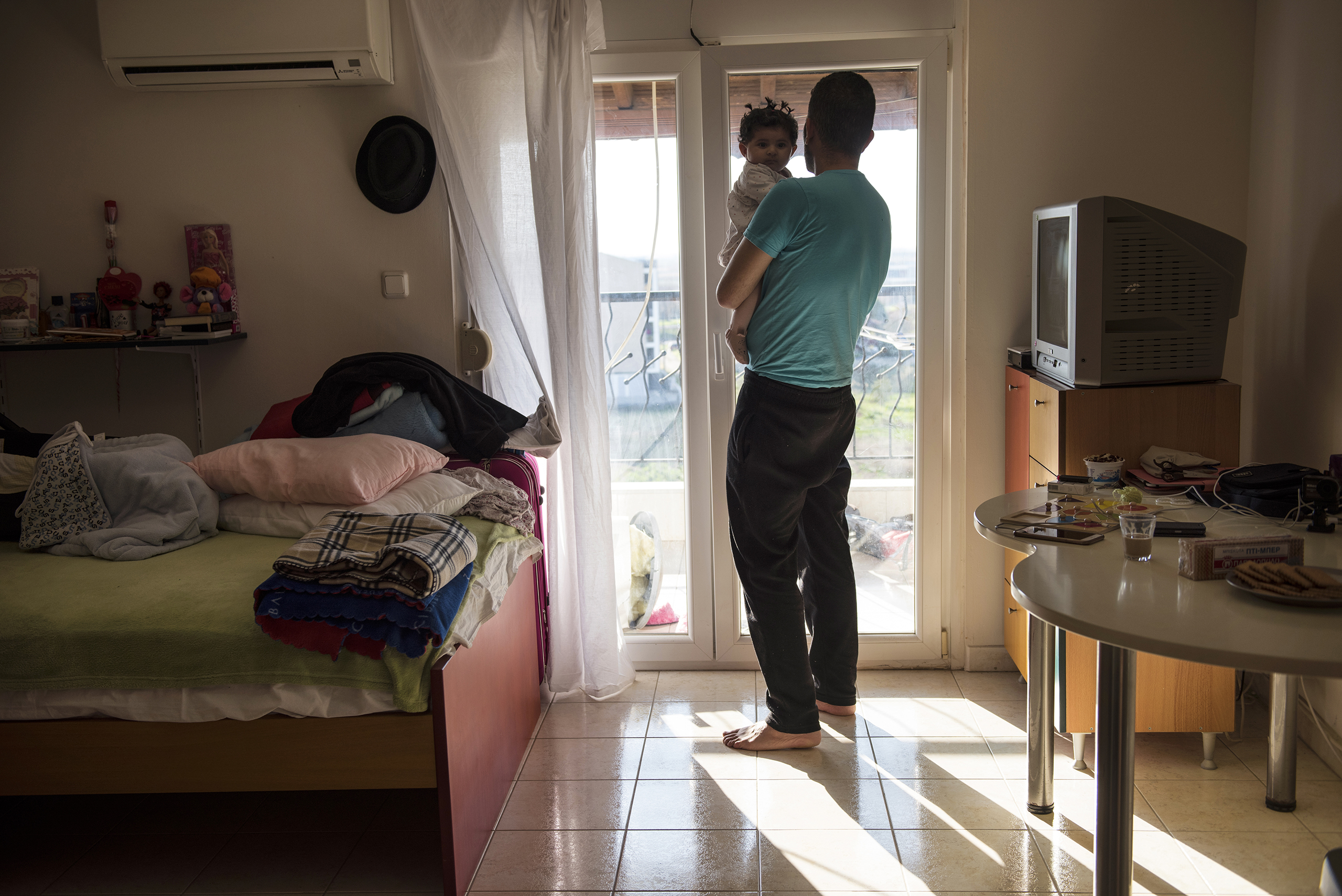 Yousuf Arsan, 27, sings to baby Rahaf, almost 6 months, while his wife (not shown) Noor Al Talaa, 22, cooks lunch at an apartment in Sidros, outside of Thessaloniki, Greece, March 28, 2017.