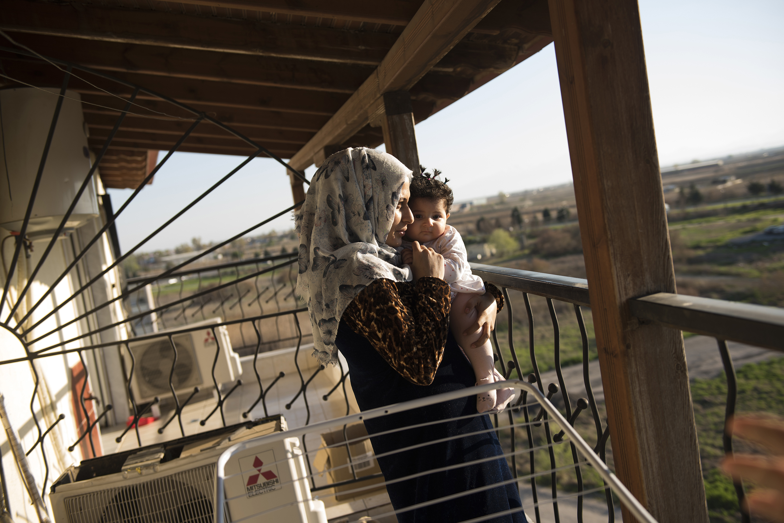 Noor Al Talaa, 22, stands on the balcony at dusk with baby Rahaf, almost 6 months, at an apartment in Sidros, outside of Thessaloniki, Greece, March 28, 2017.