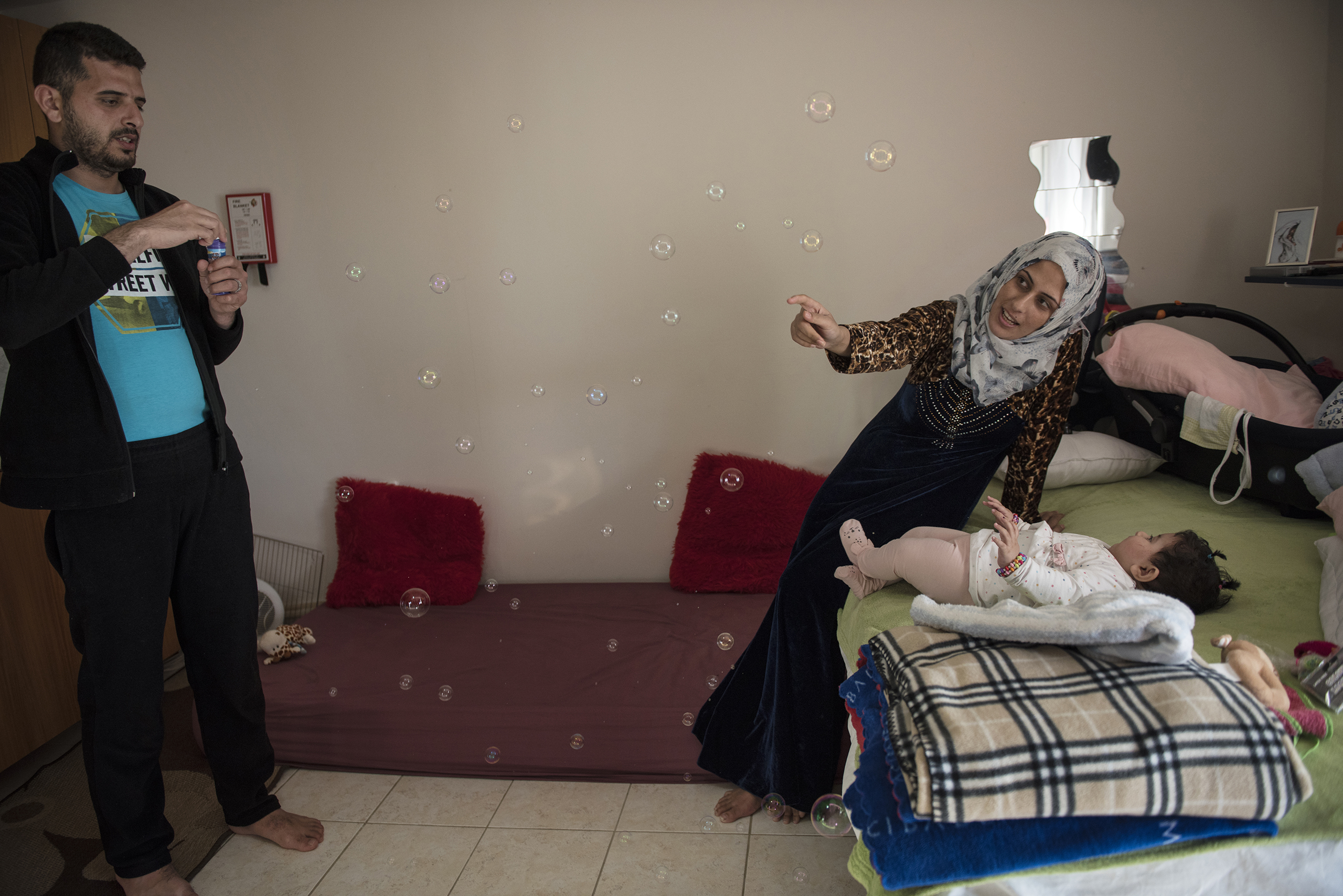 Noor Al Talaa, 22, and her husband, Yousuf Arsan, 27, entertain baby Rahaf, almost 6 months, at an apartment in Sidros, outside of Thessaloniki, Greece, March 28, 2017.