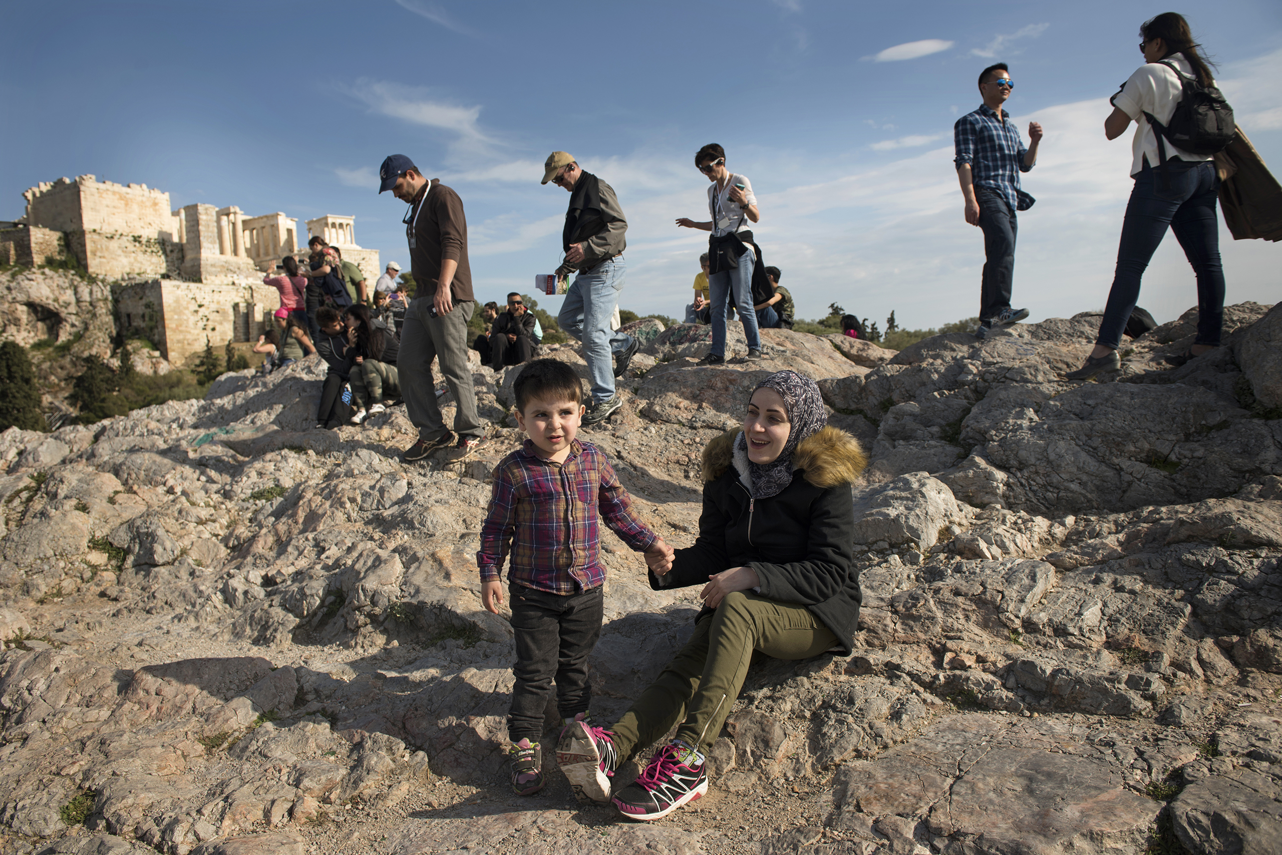 Syrian refugees Taima and her 3 year old son, Wael, walk around the Acropolis in Athens, Greece, March 30, 2017.