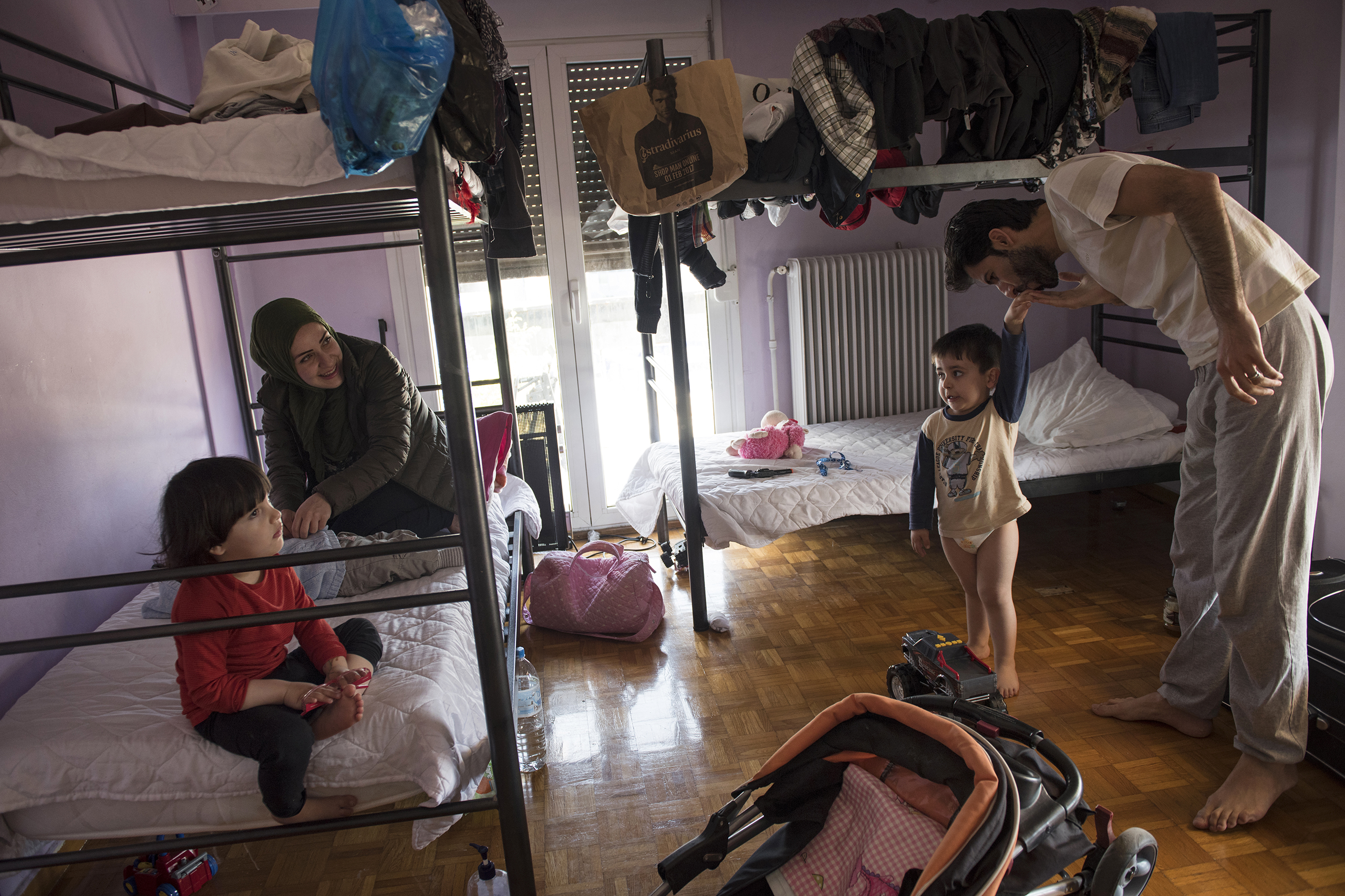 Syrian refugee, Taima, prepares to take her 6 month old daughter, Heln, for a visit to the Acropolis, while her husband, Muhannad Abzali, 28, jokes around with their other child, Wael, 3, at the temporary apartment they are staying at in Athens, Greece, March 31, 2017.
