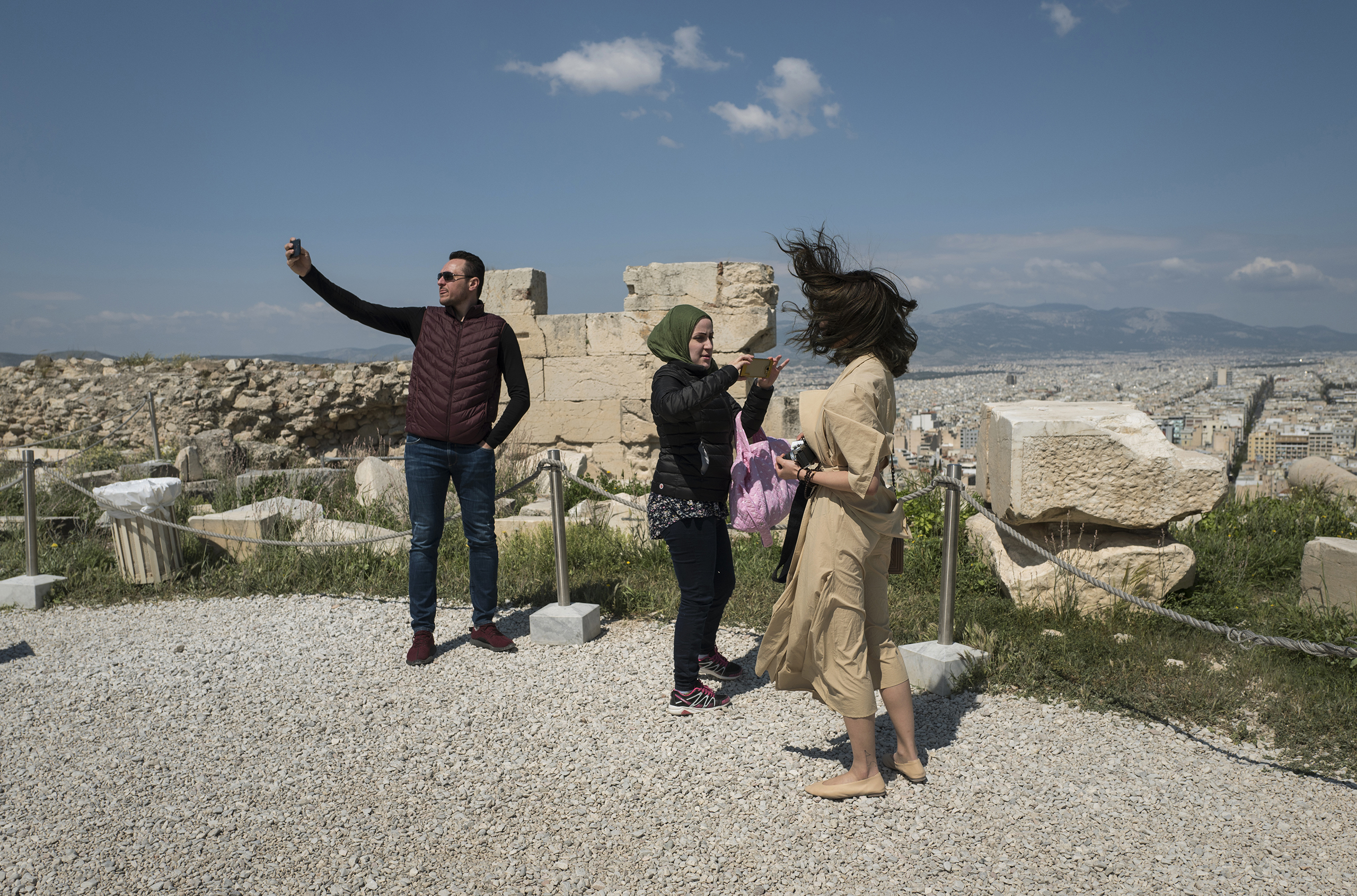Syrian refugee, Taima, takes photographs among other tourists while visiting the Acropolis in Athens, Greece, March 31, 2017.