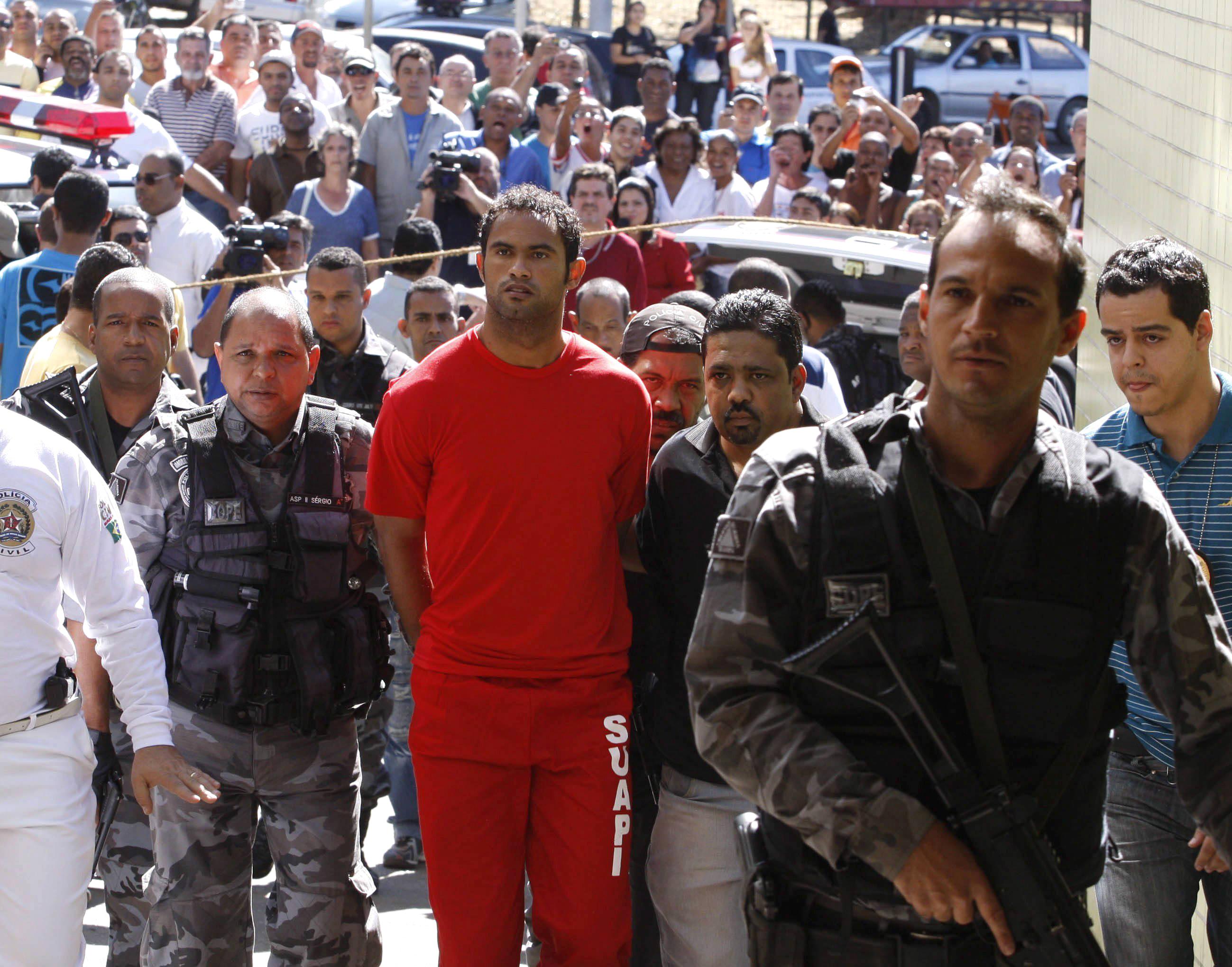 Brazilian footballer Bruno Fernandes de Souza (in red) is taken under custody to the presidium of Belo Horizonte, Brazil, on July 9, 2010.