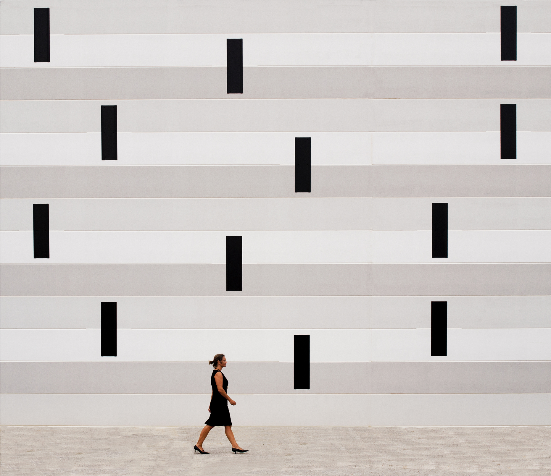 Woman walking  in font of wall with geometric shapes.