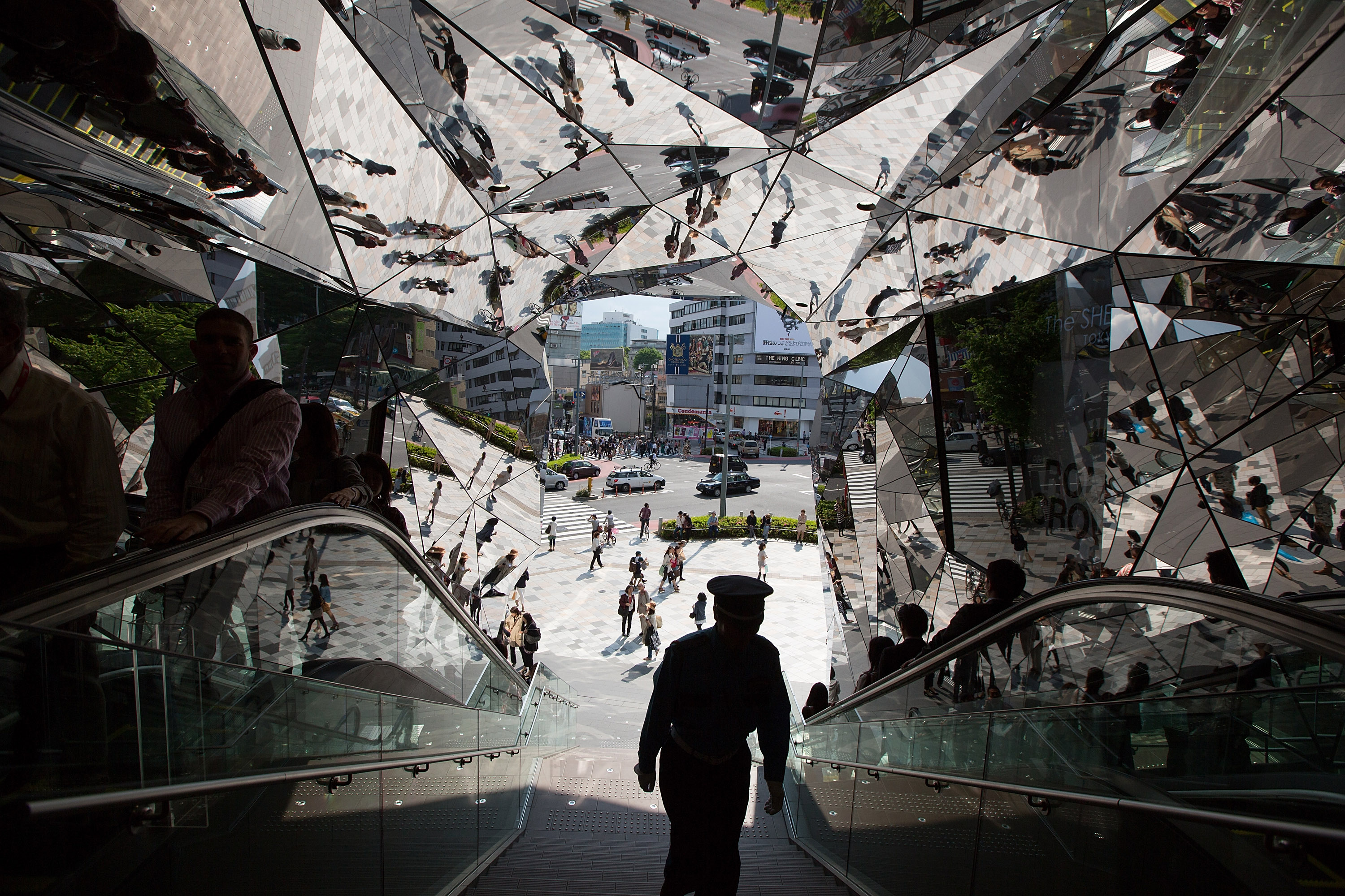Japanese shoppers and a security guard are reflected in the entrance to the 'Tokyu Plaza Omotesando Harajuku' shopping complex in Tokyo on May 11, 2012.