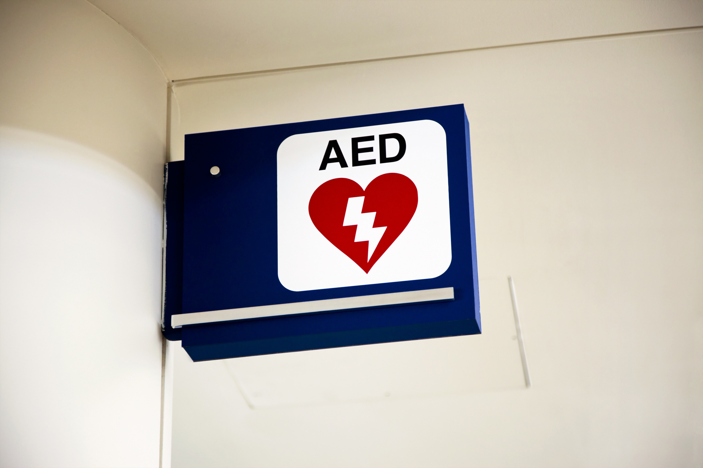 An emergency AED Automated External Defibrillator sign mounted to a wall.