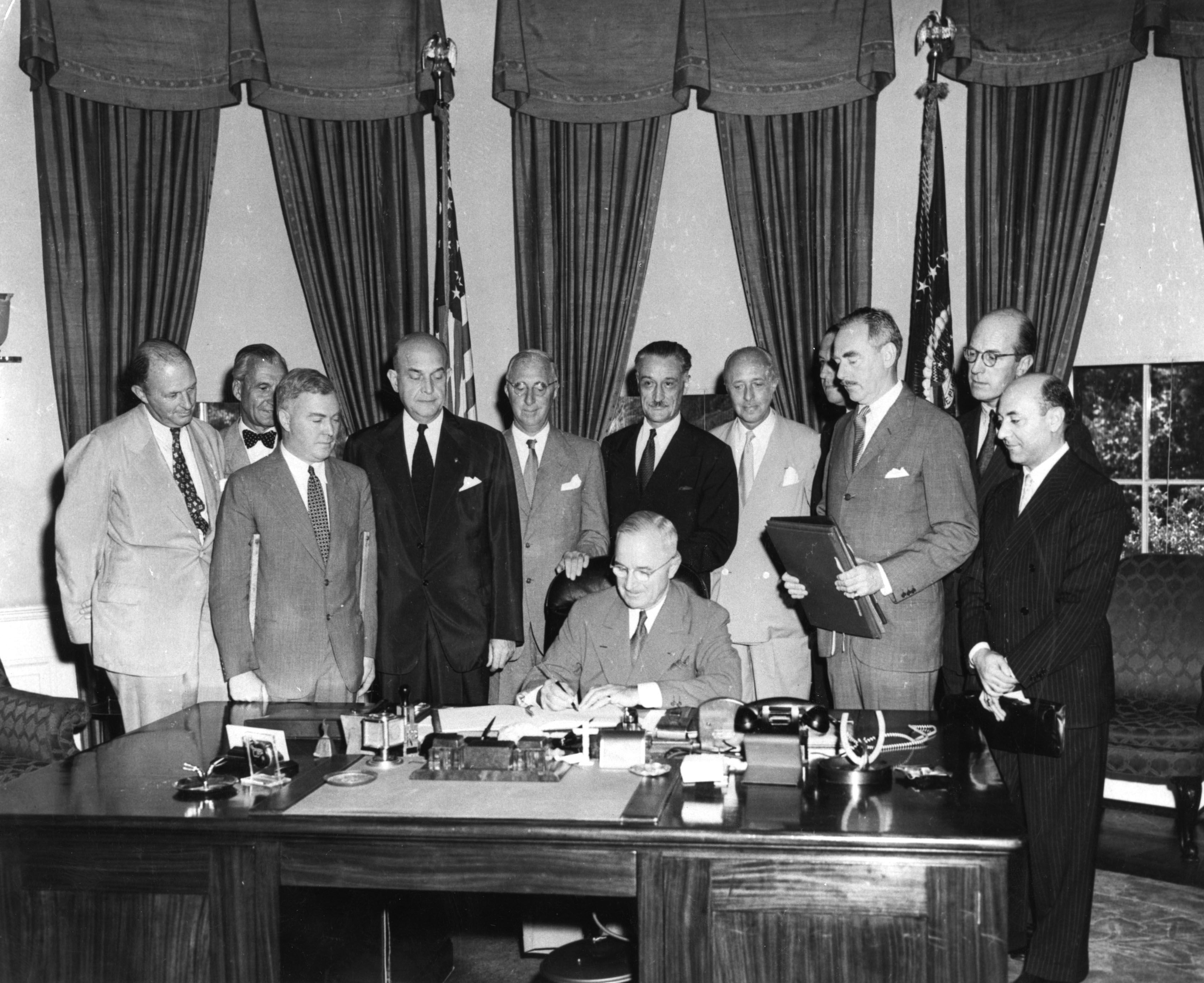 President Harry S. Truman signing the North Atlantic Treaty which marked the beginning of NATO, in a special signing ceremony on August 24, 1949. Behind him are (from left) Sir Derrick Hoyes Miller, Henrik de Kauffman, W D Matthews, Louis Johnson, Wilhelm Munthe de Morgenstienne, Henry Bonnet,  Pedro Theotonio Pereira, Dean Acheson, Jontchess reuchlin and Mario Lucienni.