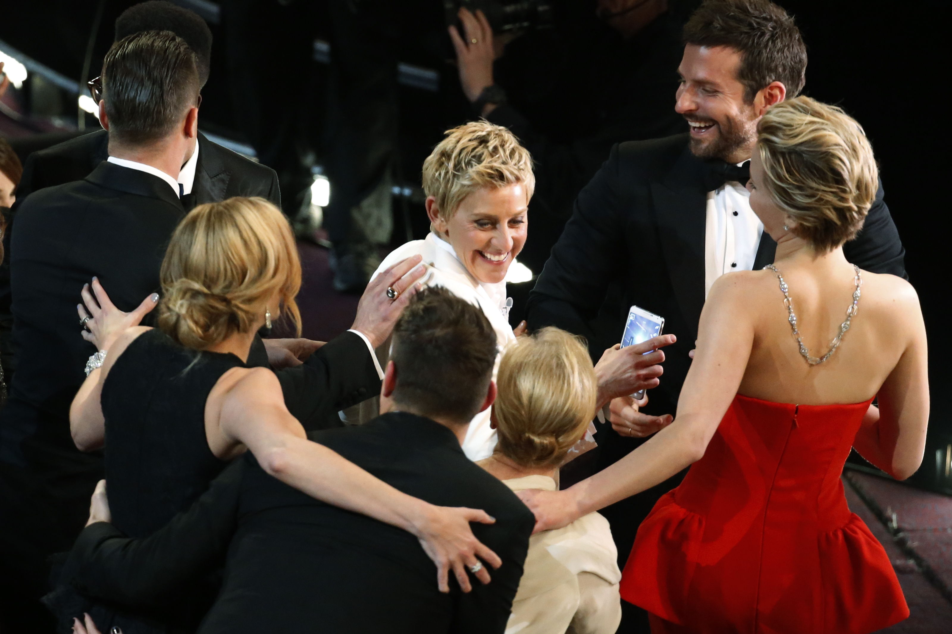 Host Ellen DeGeneres shares a laugh with Oscar nominees after taking a group  selfie  during the 86th Annual Academy Awards.