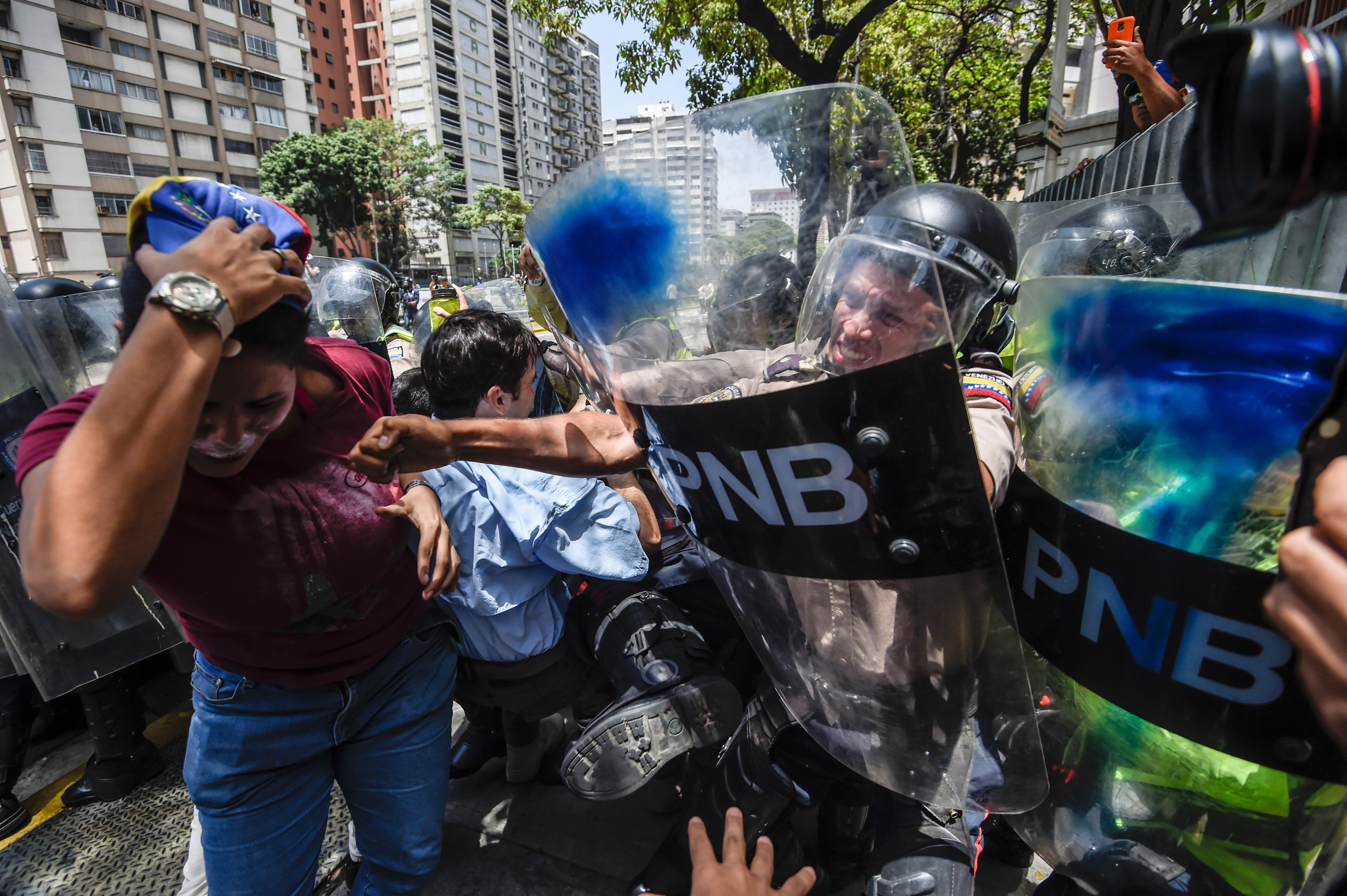 Venezuela's opposition activists scuffle with riot police during a protest against Nicolas Maduro's government in Caracas, Apr. 4, 2017.