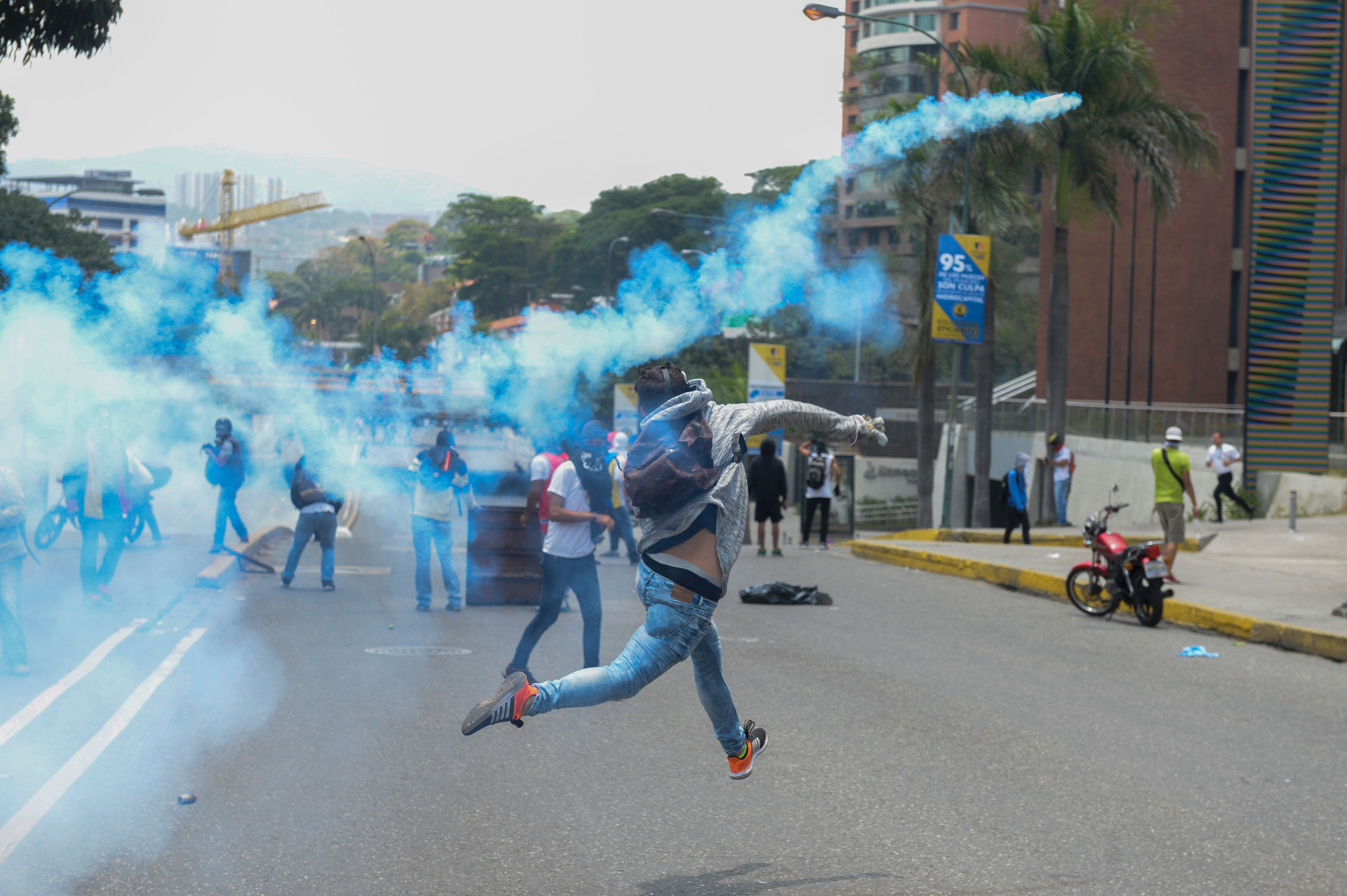 A demonstrator throws back a tear gas grenade at riot police in Caracas, Venezuela, on April 10, 2017.