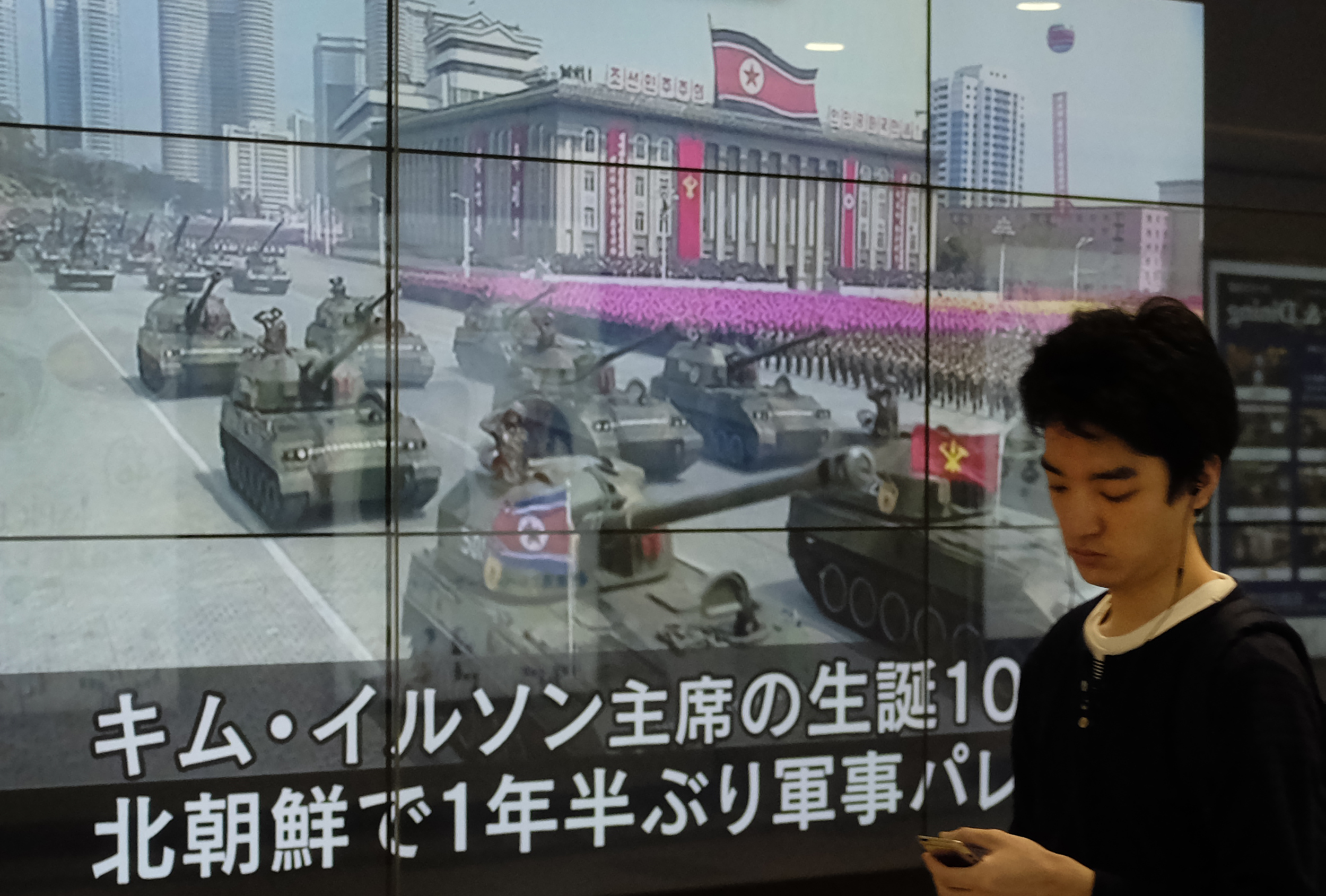 A man in Tokyo walks in front of a news video reporting a military parade marking the 105th anniversary of the birth of late North Korean leader Kim Il Sung on April 16, 2017.