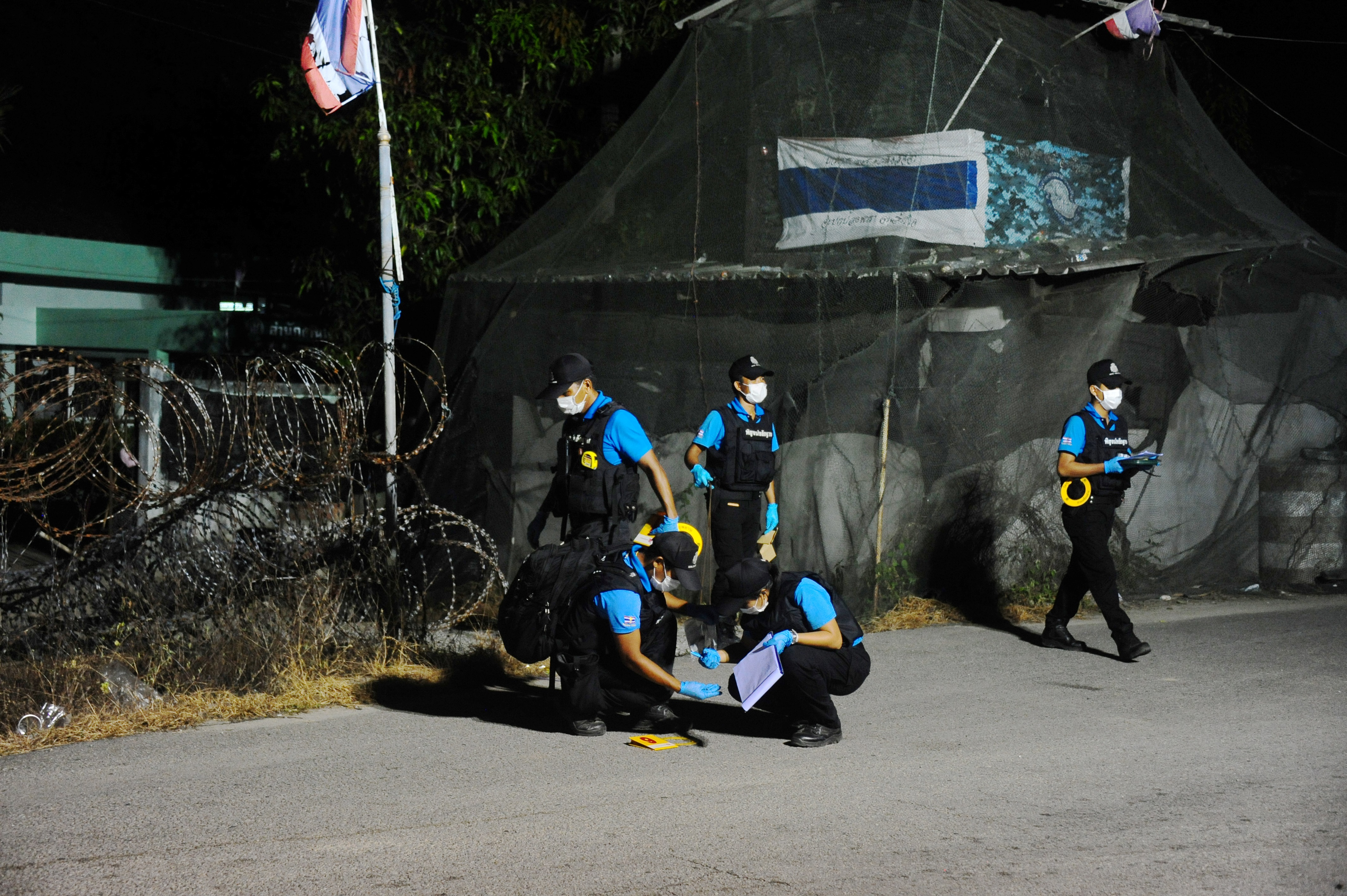 In this photo taken late on April 20, 2017 members of a forensic unit inspect the scene of a bomb blast in Thailand's southern province of Narathiwat.