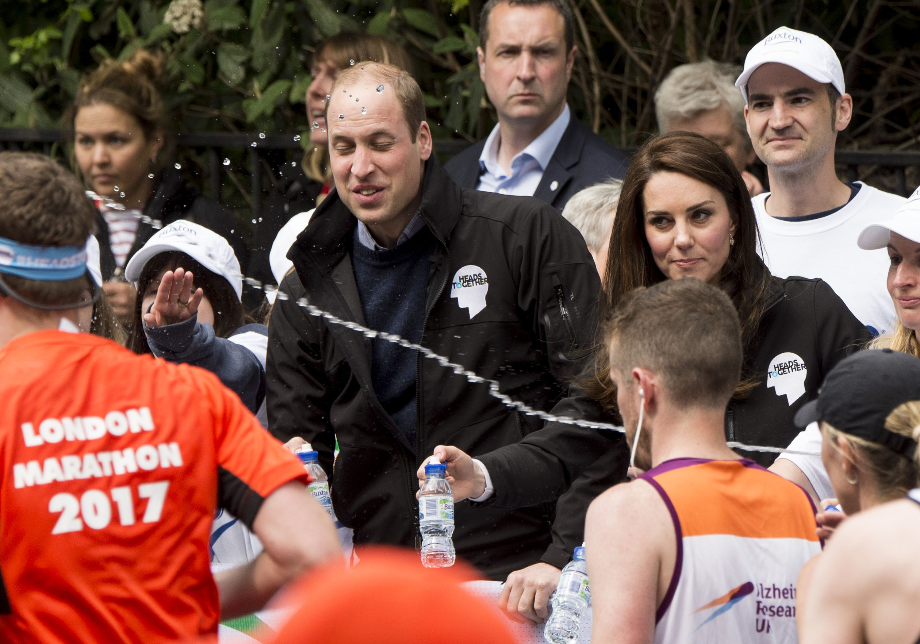 Catherine, Duchess of Cambridge with Prince William, Duke of Cambridge as he gets squirted with water at a water station during the 2017 Virgin Money London Marathon in London, England, on April 23, 2017.