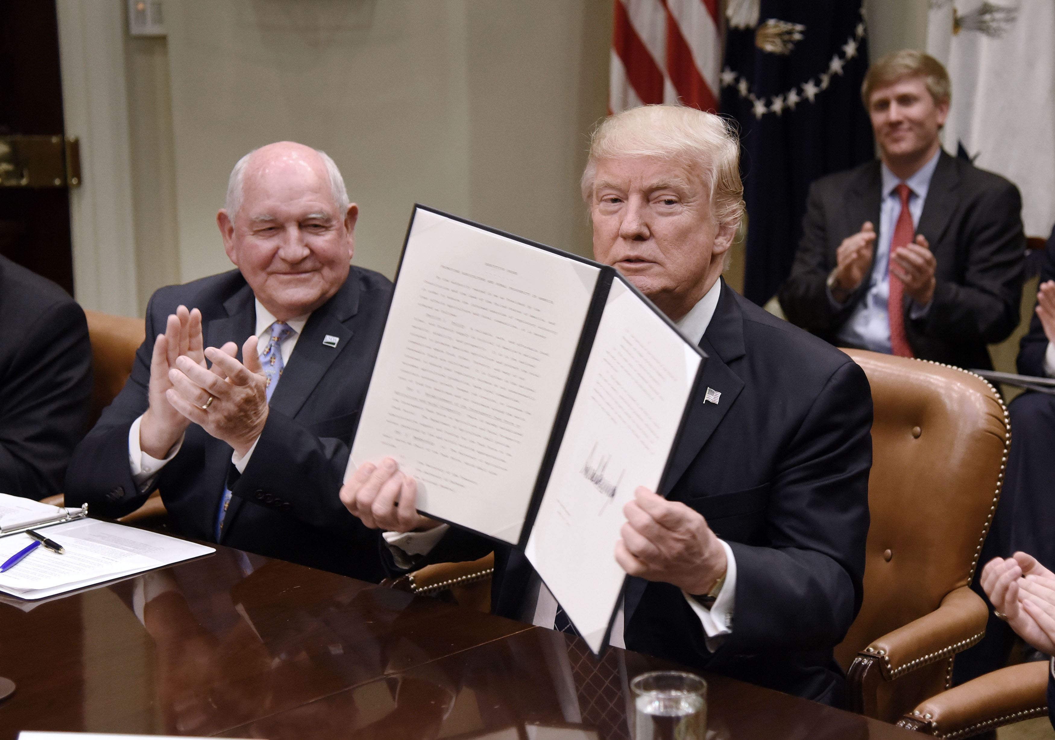 President Donald Trump signs the Executive Order Promoting Agriculture and Rural Prosperity in America as Agriculture Secretary Sonny Perdue looks on during a roundtable with farmers in the Roosevelt Room of the White House on April 25, 2017 in Washington, DC.
