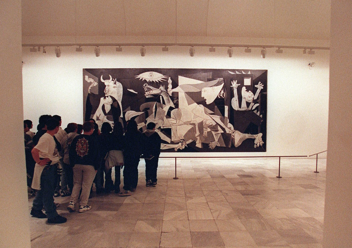 Students look at the famous Picasso painting 'Guernica' at the Queen Sofia museum in Madrid on April 23, 1997.