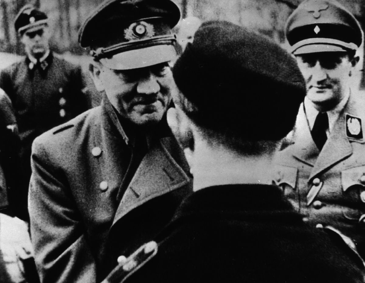 In his last official photo, Adolf Hitler (1889 - 1945) leaves the safety of his bunker to award decorations to members of Hitler Youth, in March of 1945.