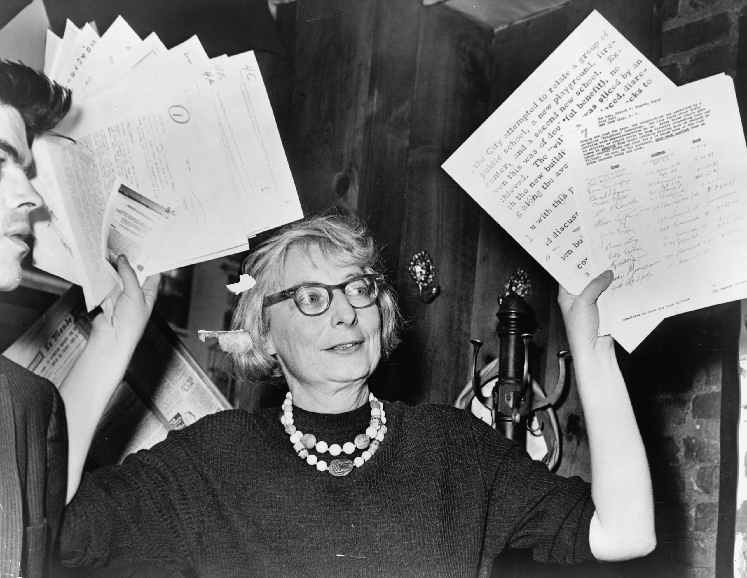 Mrs. Jane Jacobs, chairman of the Comm. to save the West Village holds up documentary evidence at press conference at Lions Head Restaurant at Hudson & Charles Streets. World Telegram & Sun photo by Phil Stanziola.