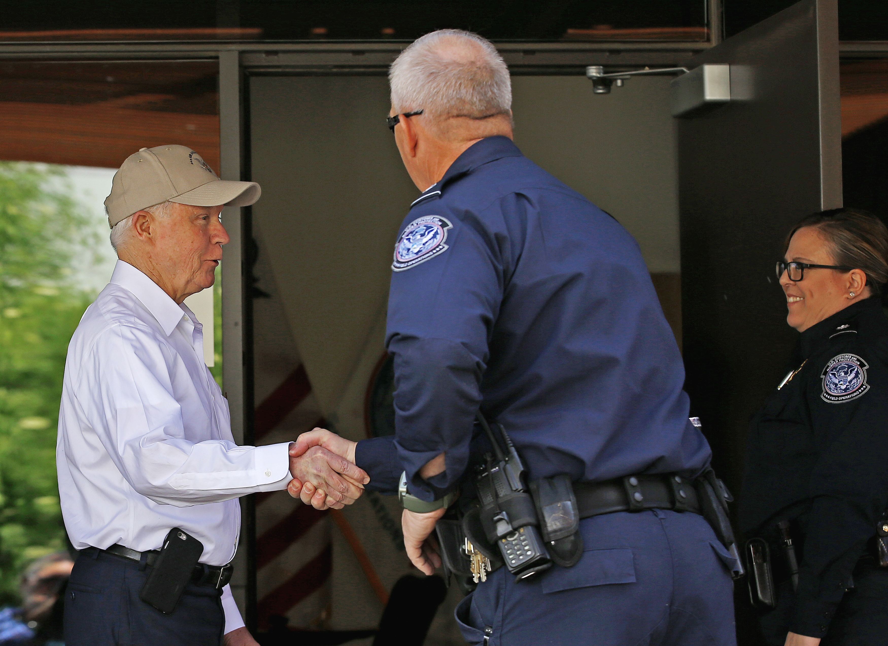 Attorney General Jeff Sessions, left, shakes hands with U.S. Customs and Border Protection officers as he tours the U.S.-Mexico border on April 11, 2017, in Nogales, Ariz.