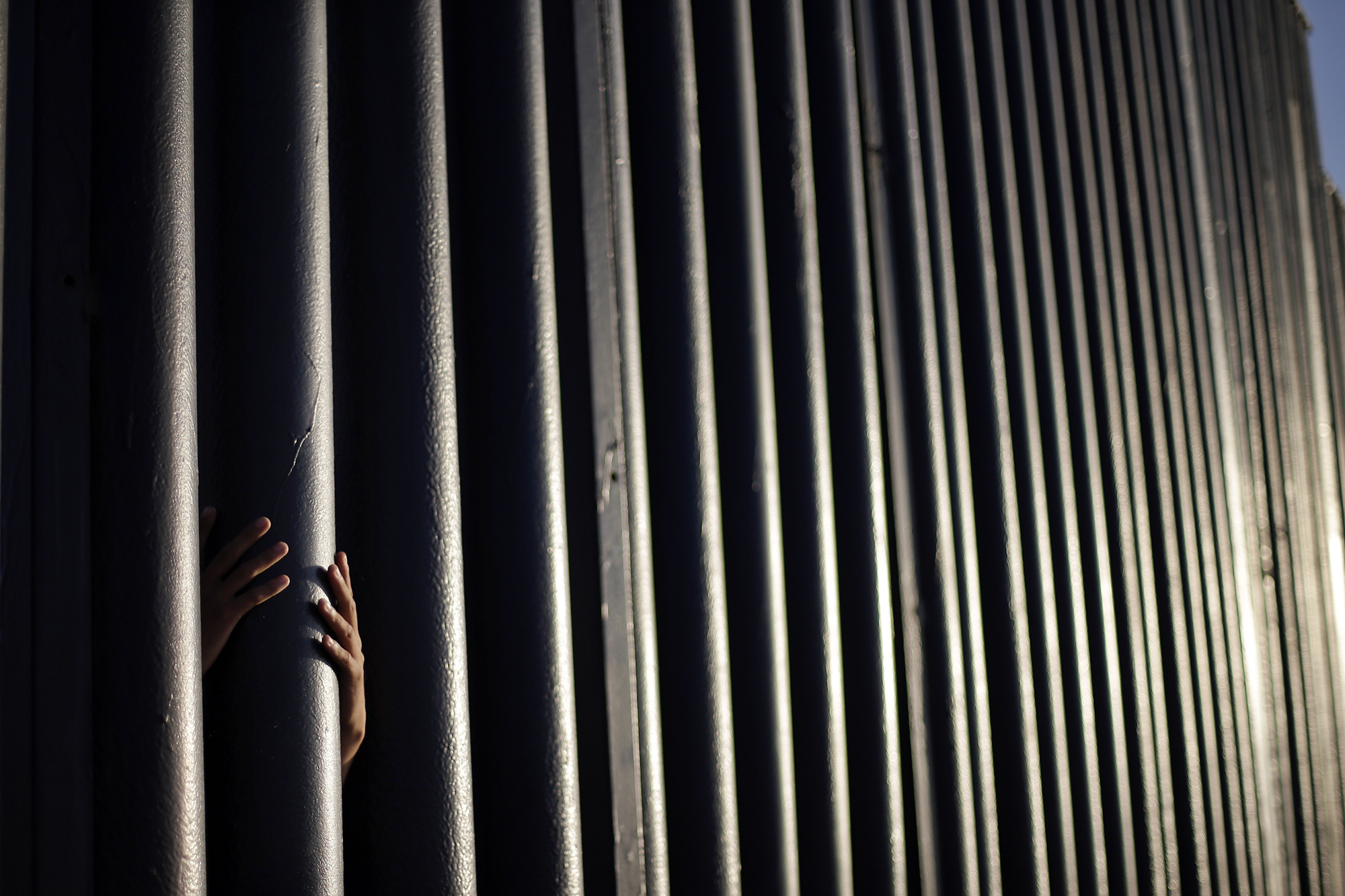 Daniel Zambrano, of Tijuana, Mexico, holds one of the bars that make up the border wall separating the U.S. and Mexico where the border meets the Pacific Ocean in San Diego, on June 13, 2013.