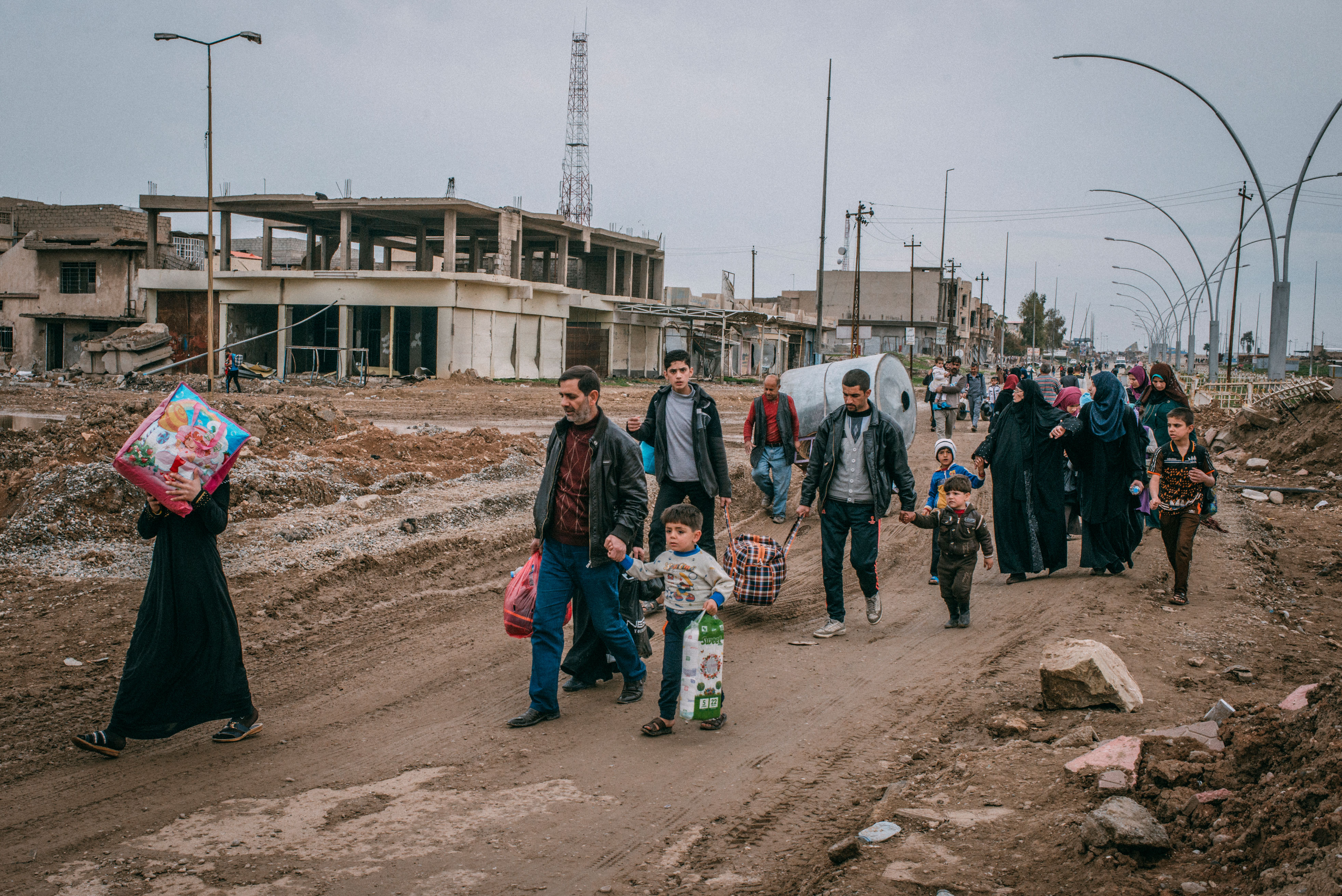 Civilians walk in Baghdad road to go back to their homes after their neighborhood has been liberated, in southwest Mosul.