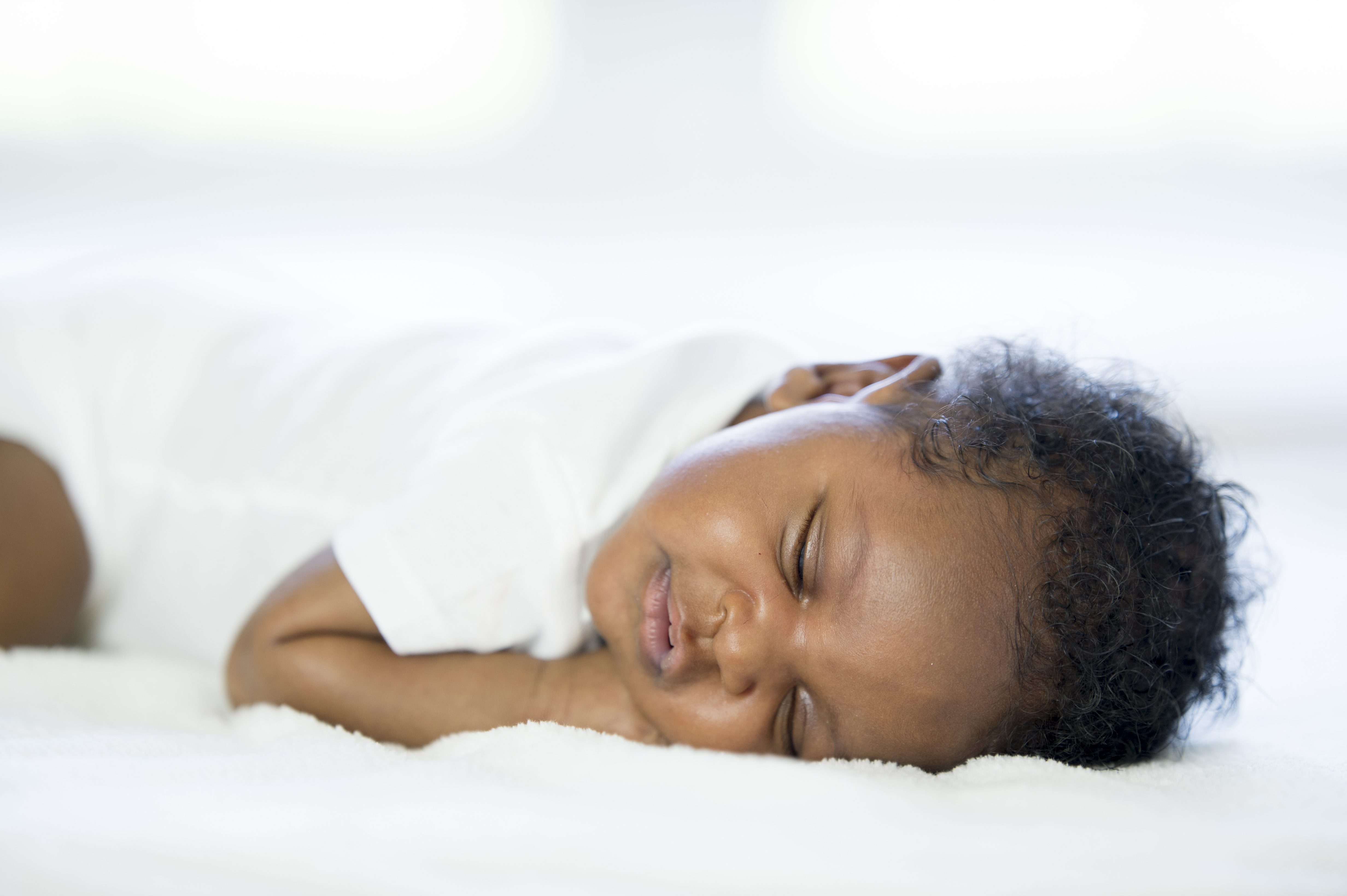 A newborn baby is lying on a while blanket and is sleeping peacefully.