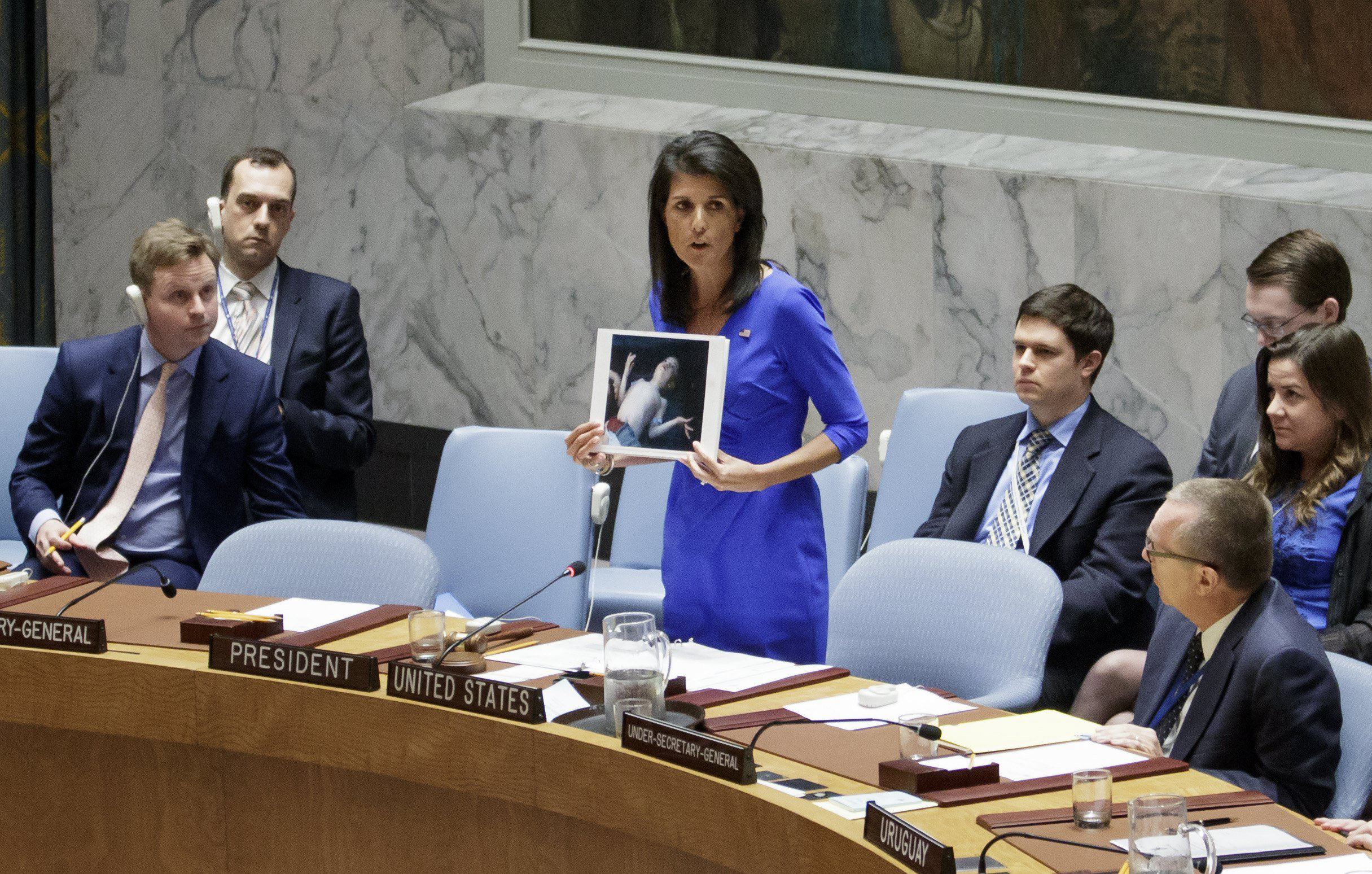 Nikki Haley, the U.S. Ambassador to the U.N., holds up pictures of victims of a chemical attack in Syria during an emergency meeting of the United Nations Security Council at the United Nations in New York on April 5, 2017.