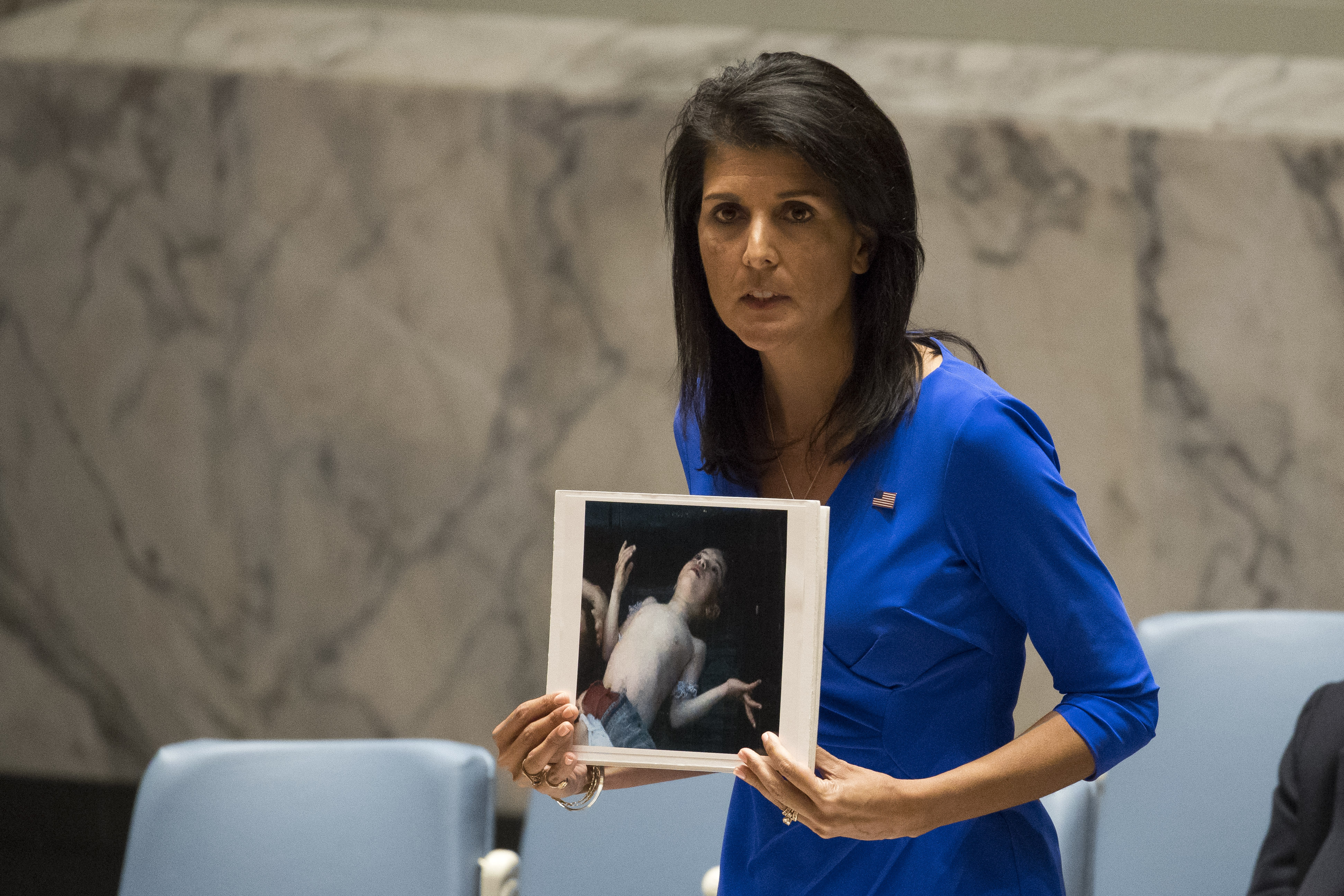 U.S. Ambassador to the United Nations Nikki Haley holds a photo of a victim of the Syrian chemical attack during a meeting of the United Nations Security Council at U.N. headquarters, April 5, 2017 in New York City.