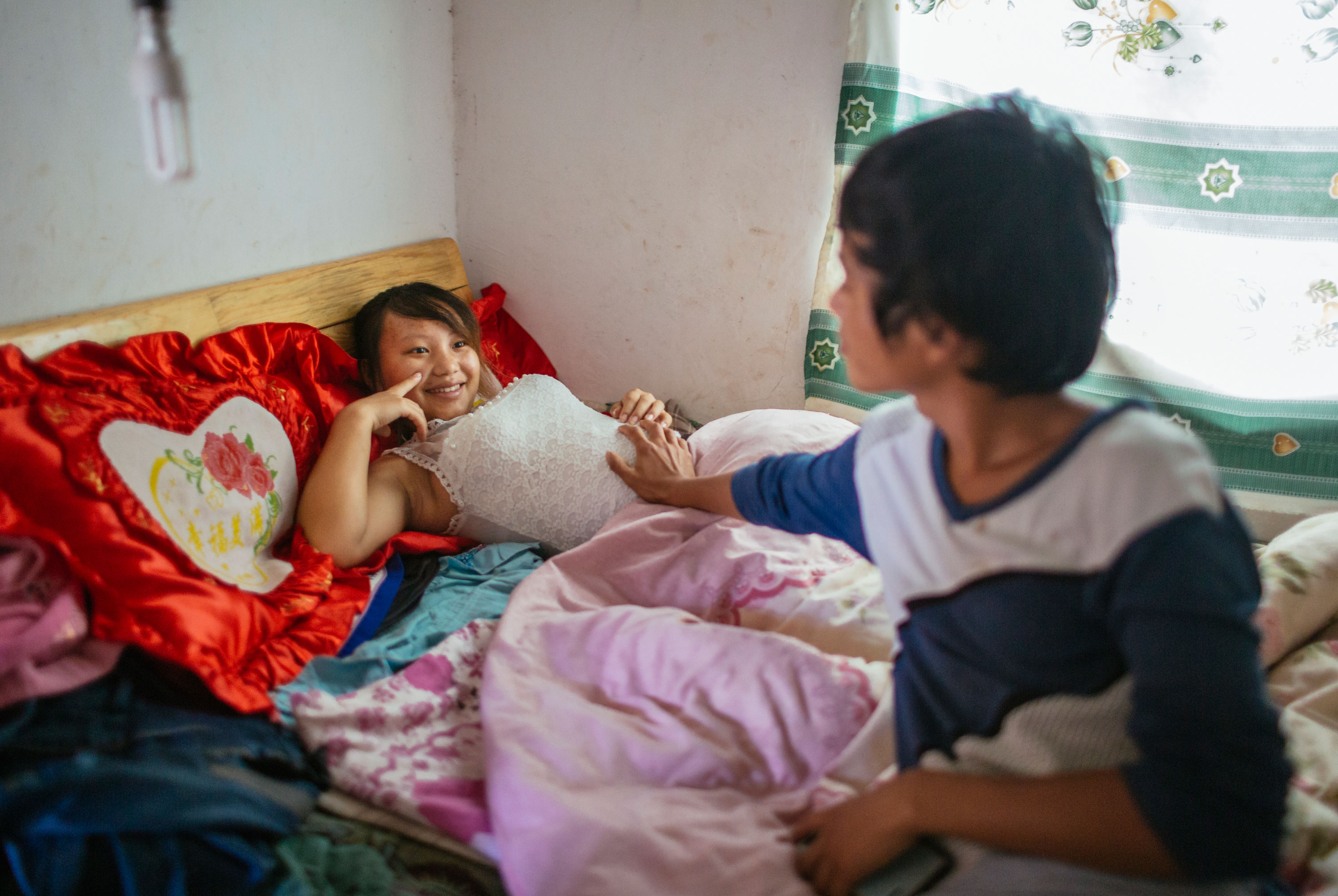 Wen touches his wife Jie's stomach to feel ther baby inside. He is 18 and she is 13 years old. They live together in Tangzibian village, Mengla county.