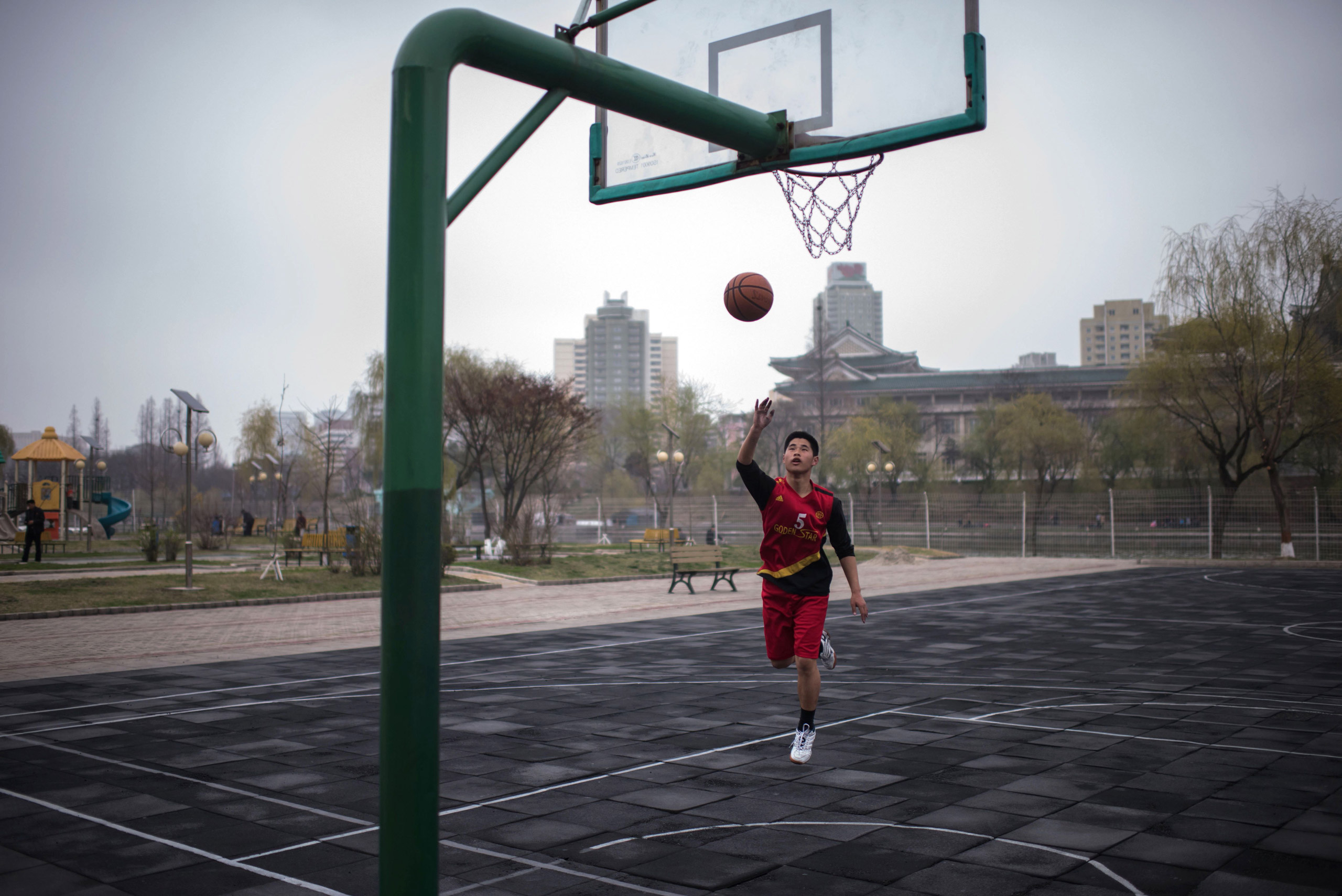 A basketball player takes a shot at the basket as he practices on a court in Pyongyang on April 8, 2017.