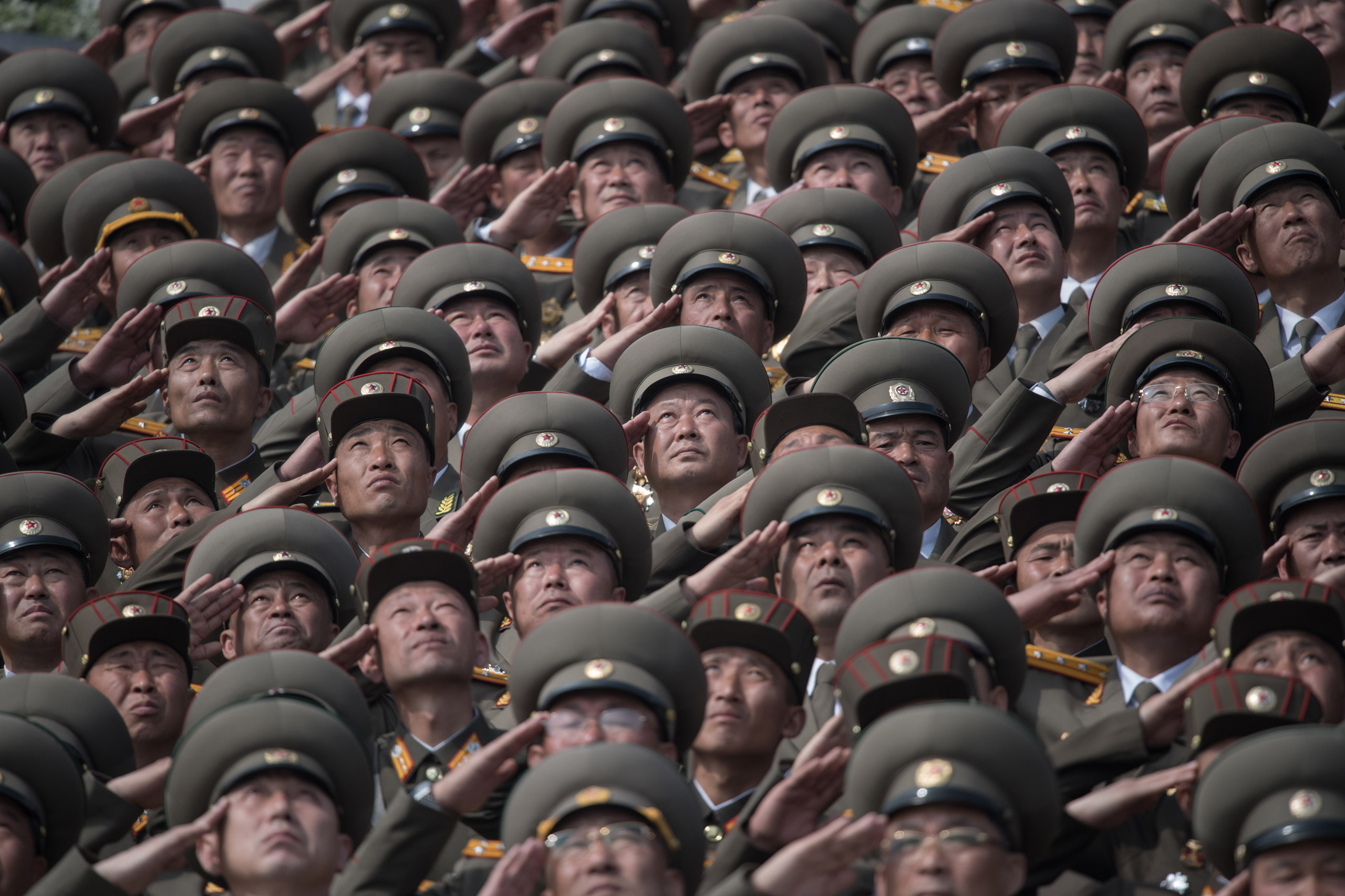 Korean People's Army (KPA) soldiers salute as they watch a military parade marking the 105th anniversary of the birth of late North Korean leader Kim Il-Sung, in Pyongyang on April 15, 2017.