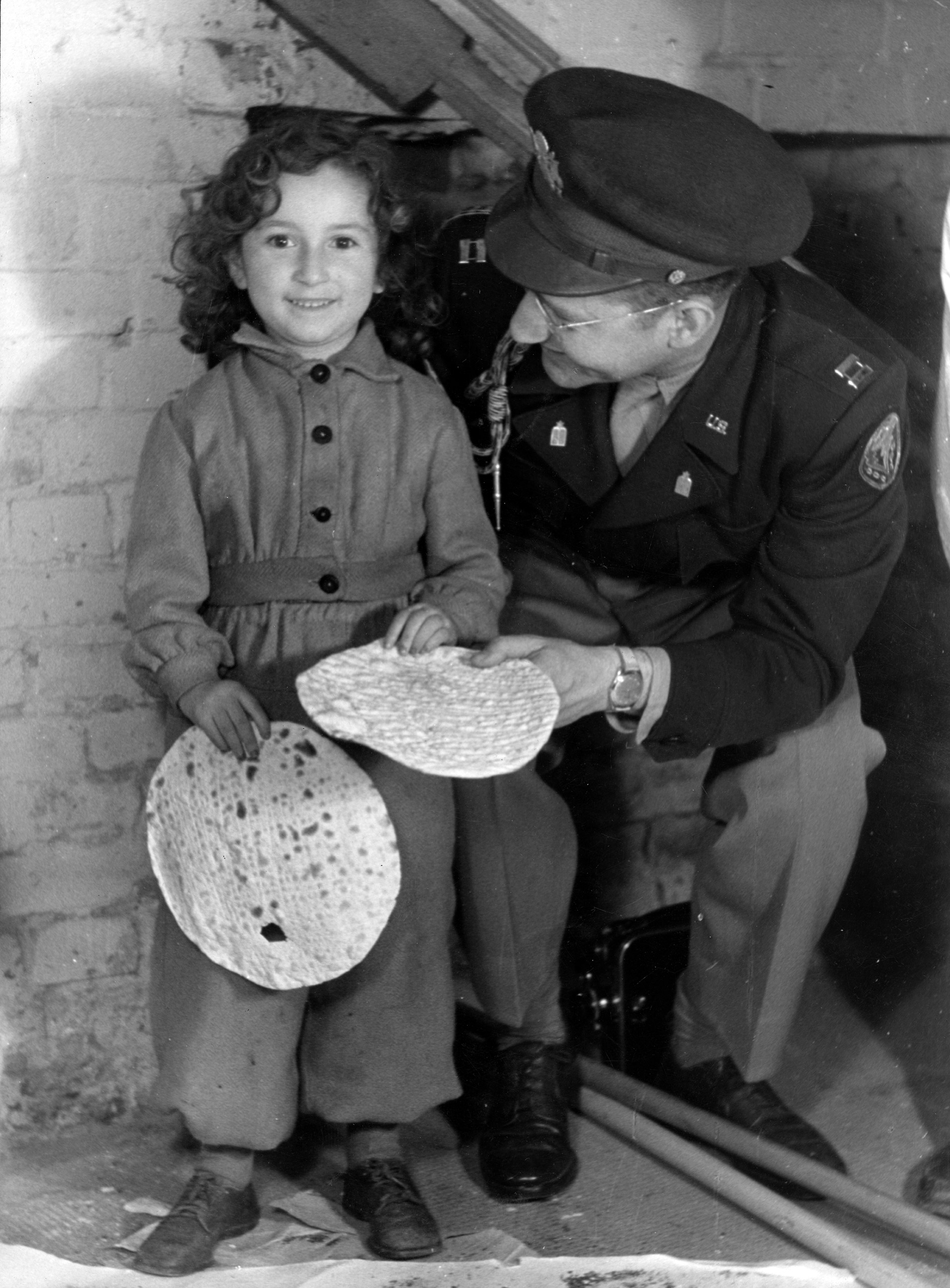 A young girl from the Berlin-Mariendorf DP Camp holding a round shmurah matzo. With her is Captain J. Robbins, Jewish Chaplain for Berlin. Berlin-Mariendorf, Germany, c. 1947. Photographer: Alois Bankhardt.
