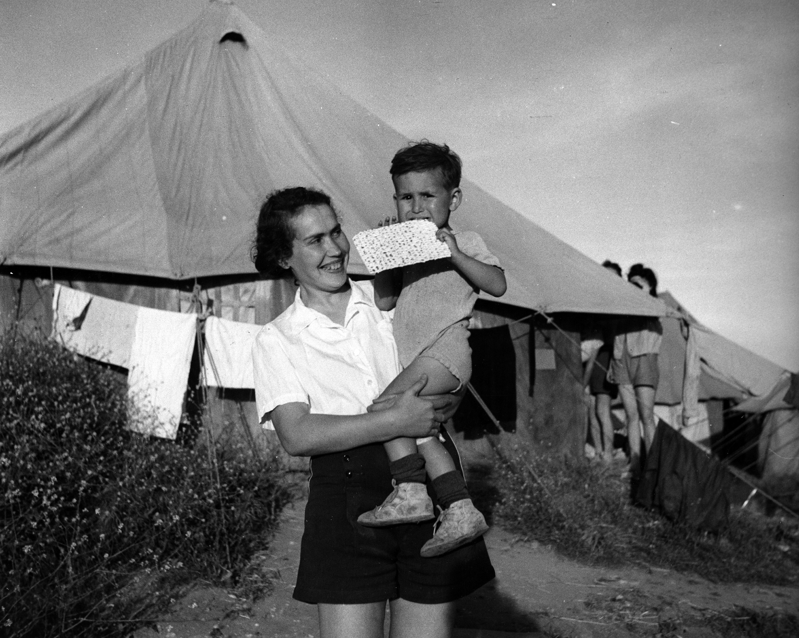 A Jewish refugee from Cracow at the detention camp holds her 2-year-old son while he eats Passover matzo. Holiday supplies were furnished by JDC. Caraolos, Cyprus. c. 1947. Photographer: Al Taylor.