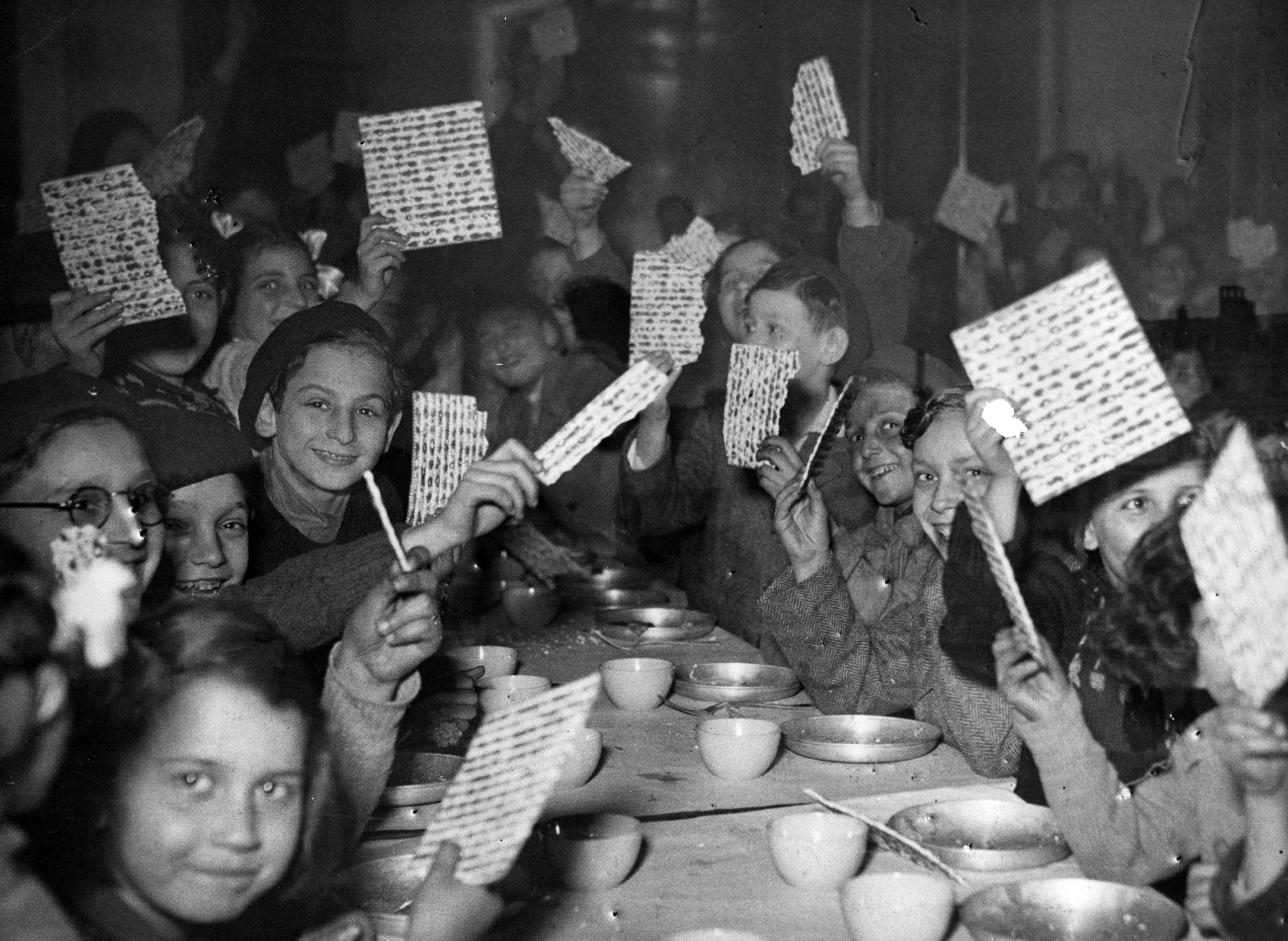 Young refugees at a Passover Seder holding up their matzot with pride at a children's canteen run by the JDC partner Federation des Societes Juives en France. France, c. 1947. Photographer unknown.