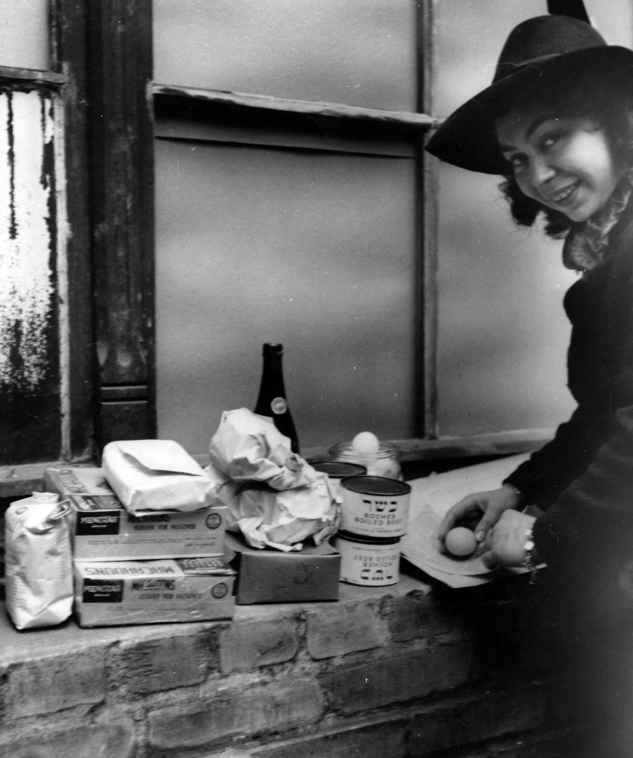 Woman with provisions supplied by JDC as part of Passover distribution. In an effort to give meaning to the first Passover spent in freedom after a decade under Nazi terror, JDC supplied over 2 million pounds of Passover supplies. Berlin, Germany, c. 1946. Photographer: Fritz Eschen, Eschen-Studio.