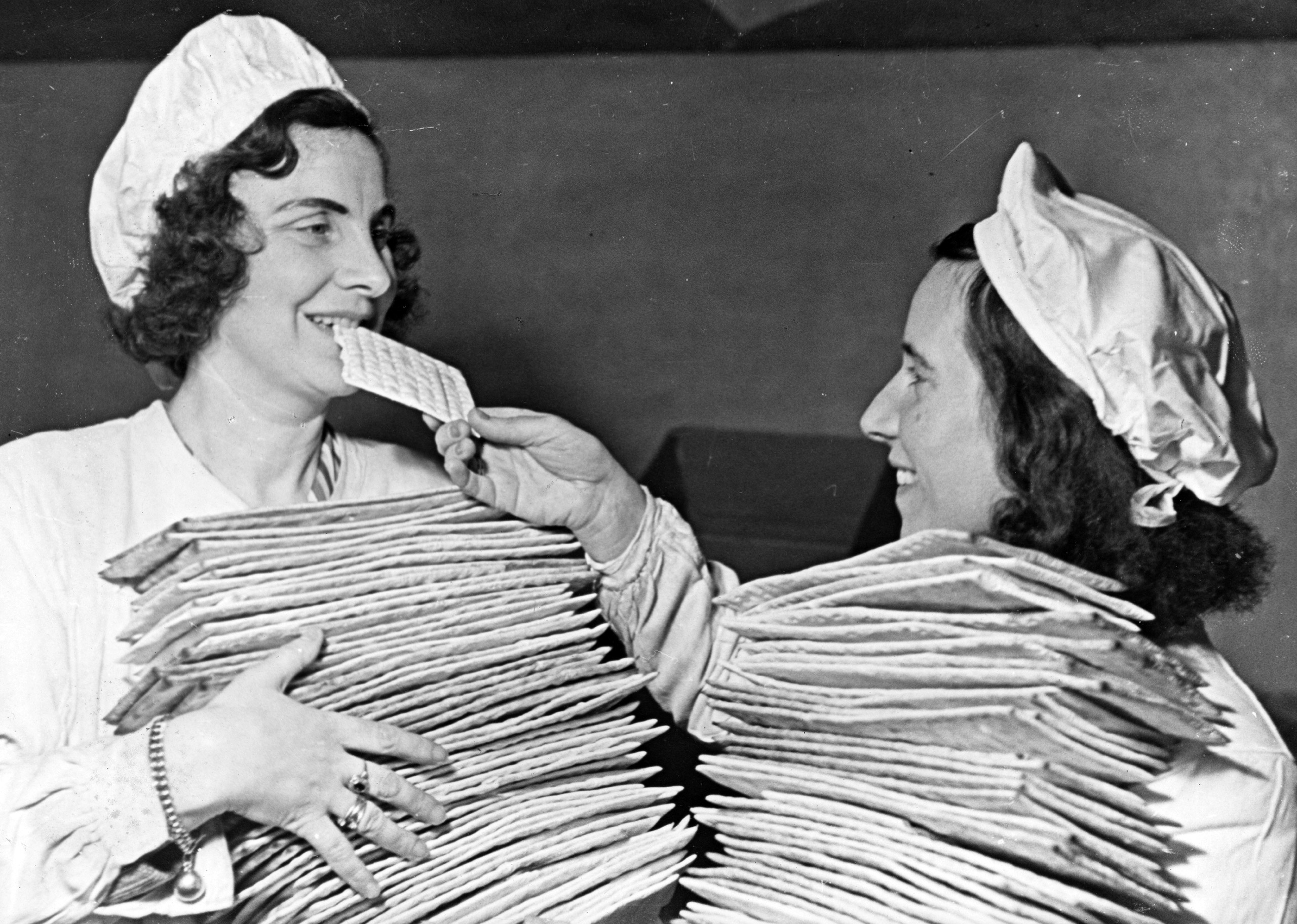 Two young women in the Sarotti Fabrik Bakery, where a goal of 85,000 pounds of matzo for Passover was set after a 10 year closure by official edict. Berlin, Germany, 1946. Photographer unknown.